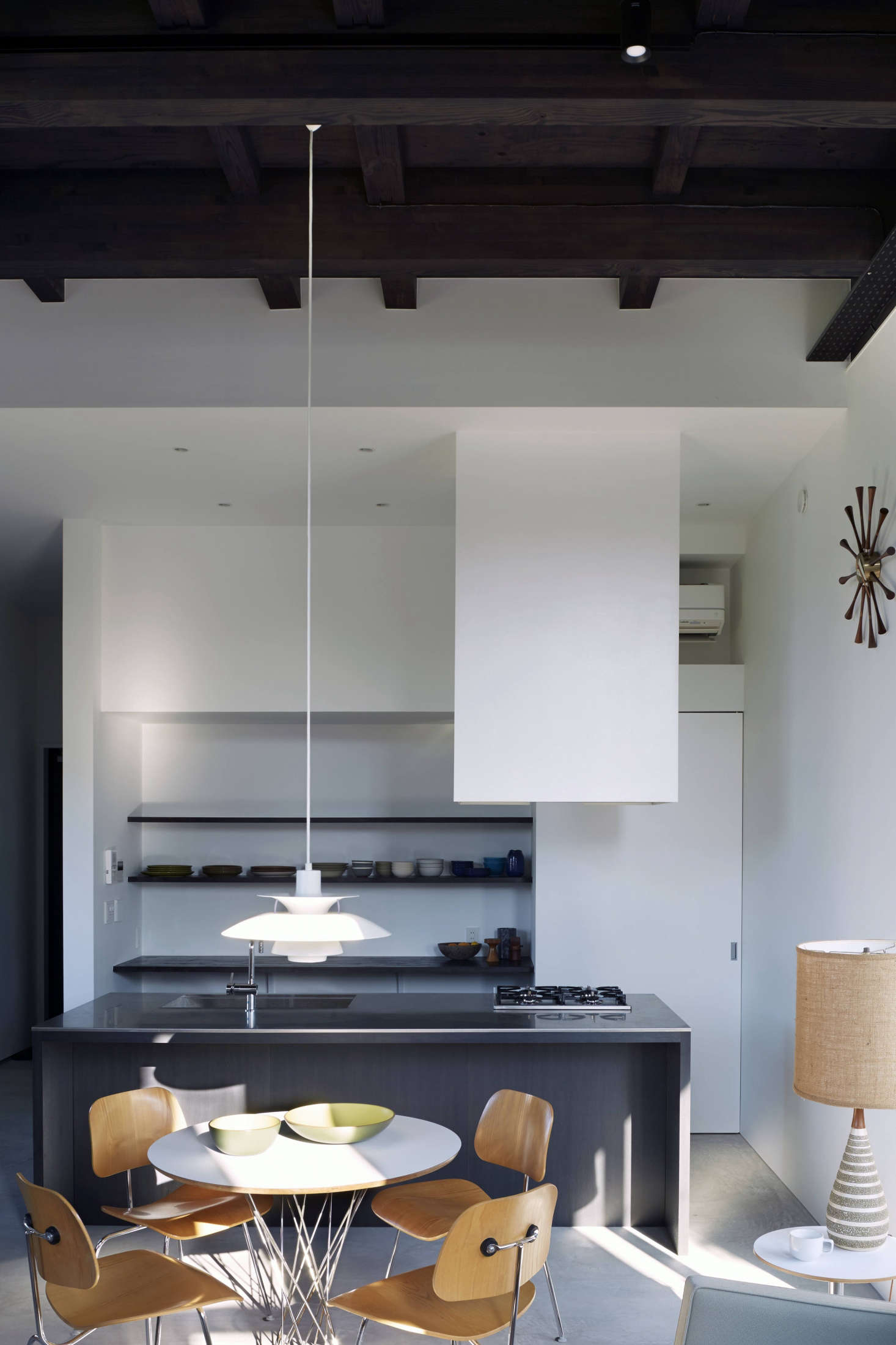 "The kitchen is set off by a stainless-steel-topped stained oak island modeled after a Donald Judd piece. It has a four-burner cooktop, the standard size in Japan, and a Sheetrock-encased hood that extends from the ceiling: ""sculptural and affordable,"" says Taka."