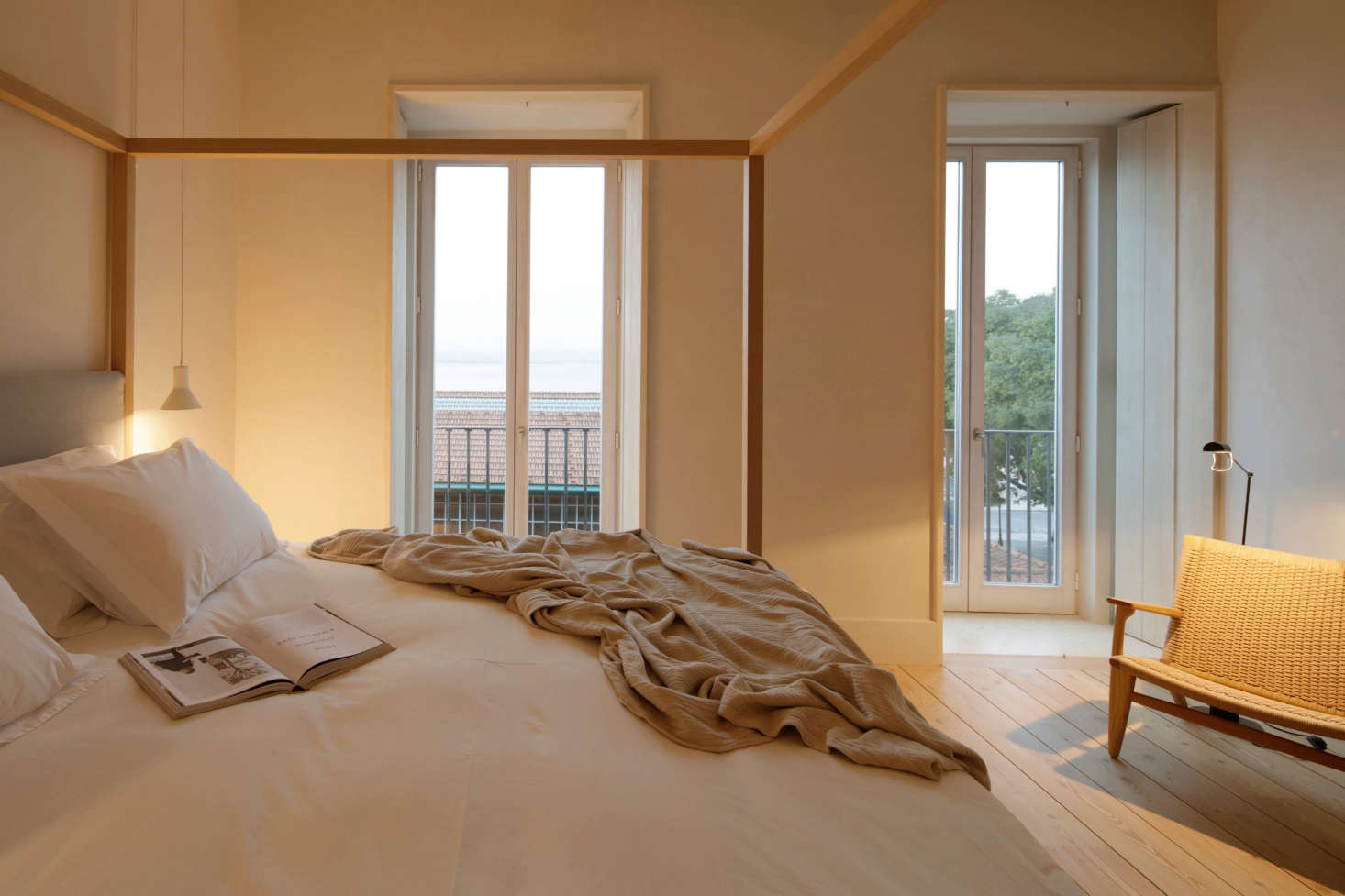The four-poster beds are byMaxalto from B&B Italia, the cotton-linen mattresses are by Alma Natura, and the pillows and blankets are made locally. A CH25 Lounge Chair by Carl Hansen sits in the corner.