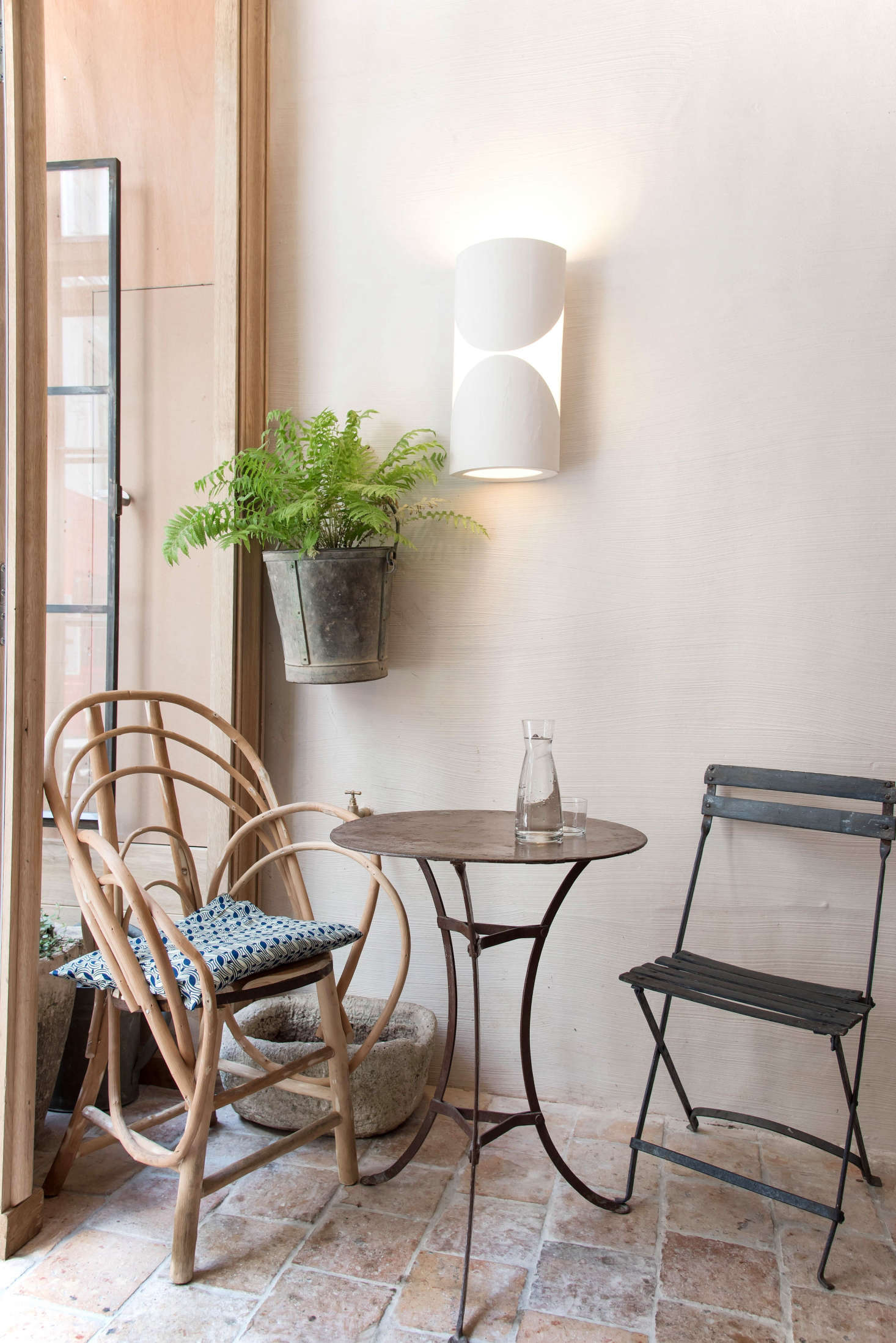 The front terrasse room has the feel of a laid-back garden in a generations-old family estate, thanks to mix-and-match vintage garden furniture that de Villeneuve sourced from flea markets andbrocantes in the South of France. For easy charm, follow suit: Mix indoor with outdoor chairs, cane with metal, and a cushion or two. (The plaster lights were designed by Champsaur.)