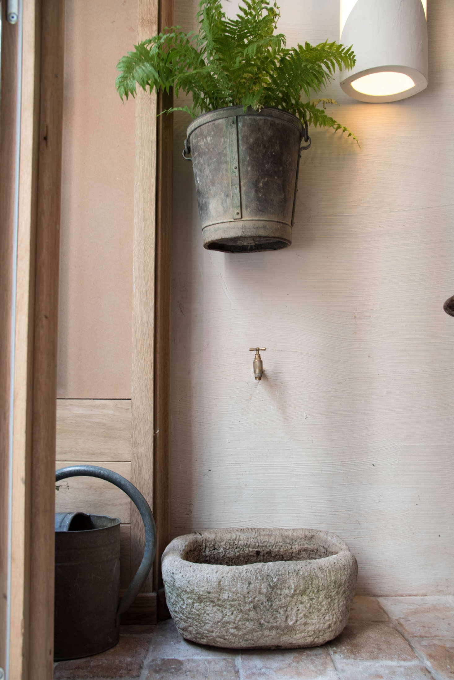 For a respite from the heat, add elements from the garden. In a quirky vignette by the front window: A copper spigot in the wall is positioned above a stone basin, a flea market find which will soon house herbs.