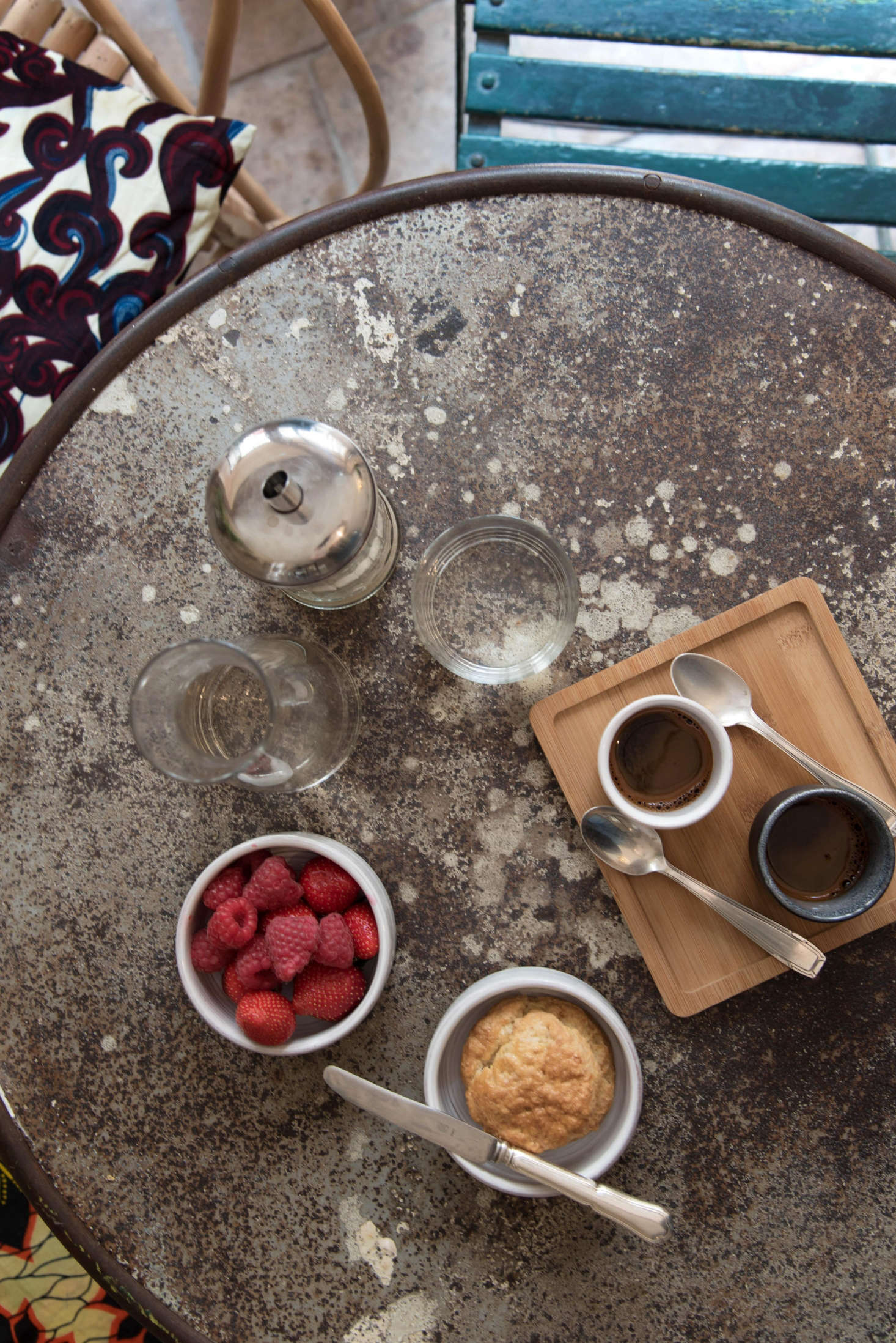 """On a vintage cafe table, ceramics by an Italian artisan living in Belgium mix with Japanese wooden trays and """"classical glassware for French bistros."""" Simple shapes keep it cohesive."""