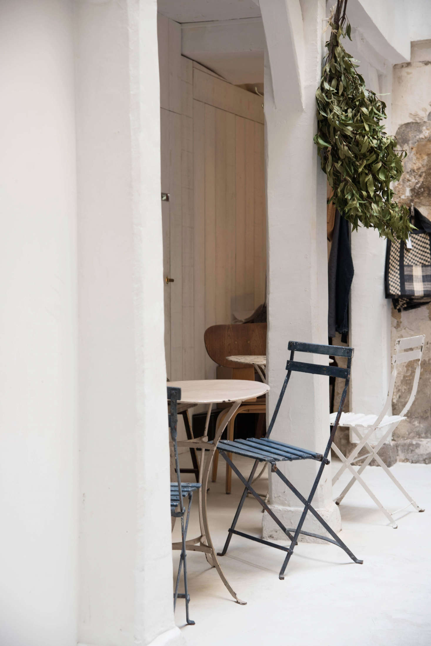 """De Villeneuve and Champsaur took cues from the feel of each section within the """"atypical long space."""" Here, a high-ceilinged area was left bright and open, beams and archways become niches for dining, and vintage cafe furniture in muted hues doesn't compete with room's light and simple lines."""