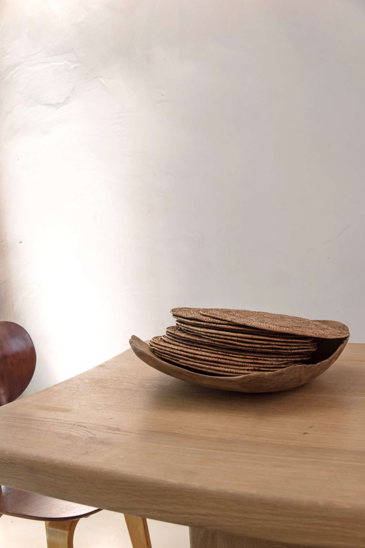 """For an impromptu table setting, stack napkins, placemats, and glassware on the table and set out vintage baskets heaping with flatware. Here, woven placemats become a design object when set in a wooden bowl. (De Villeneuve sourced design elements that would feel """"in line with the products that I was sourcing: grains, flour, olive oil, almonds, etc., coming from Sicilia, South of France, Mallorca""""—the placemats are from Mauritius.)"""