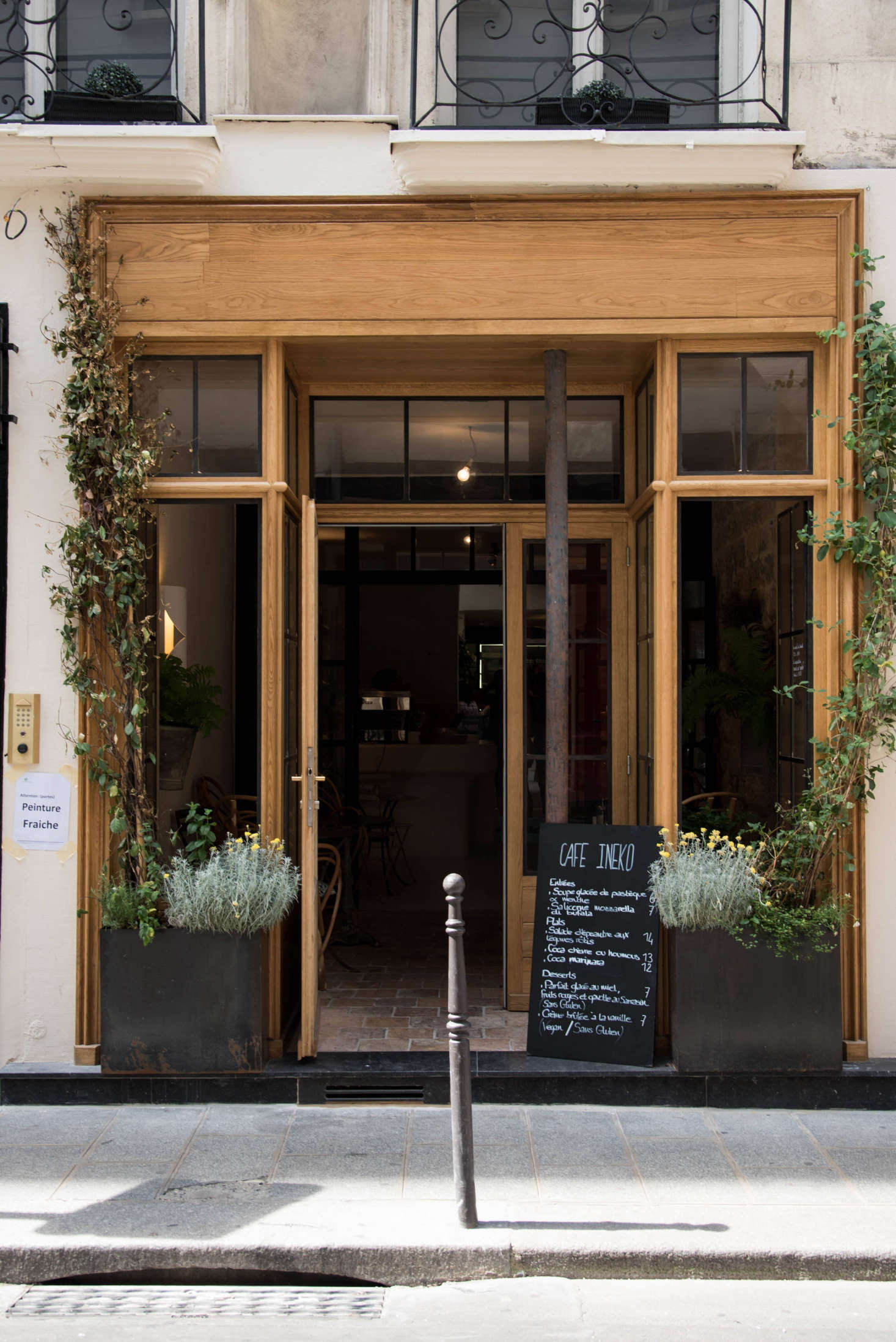 """Consider curb appeal: To invite passerby into Café Ineko, de Villeneuve and Champsaur transformed the facade with new wood trim. """"The building is from the 17th century and protected,"""" de Villeneuve says, so after getting special authorization from the city, they tread carefully to upgrade the exterior (and the interiors) with respect to its history. Potted plants, custom steel-frame doors and windows, and trailing vines add to the charm."""