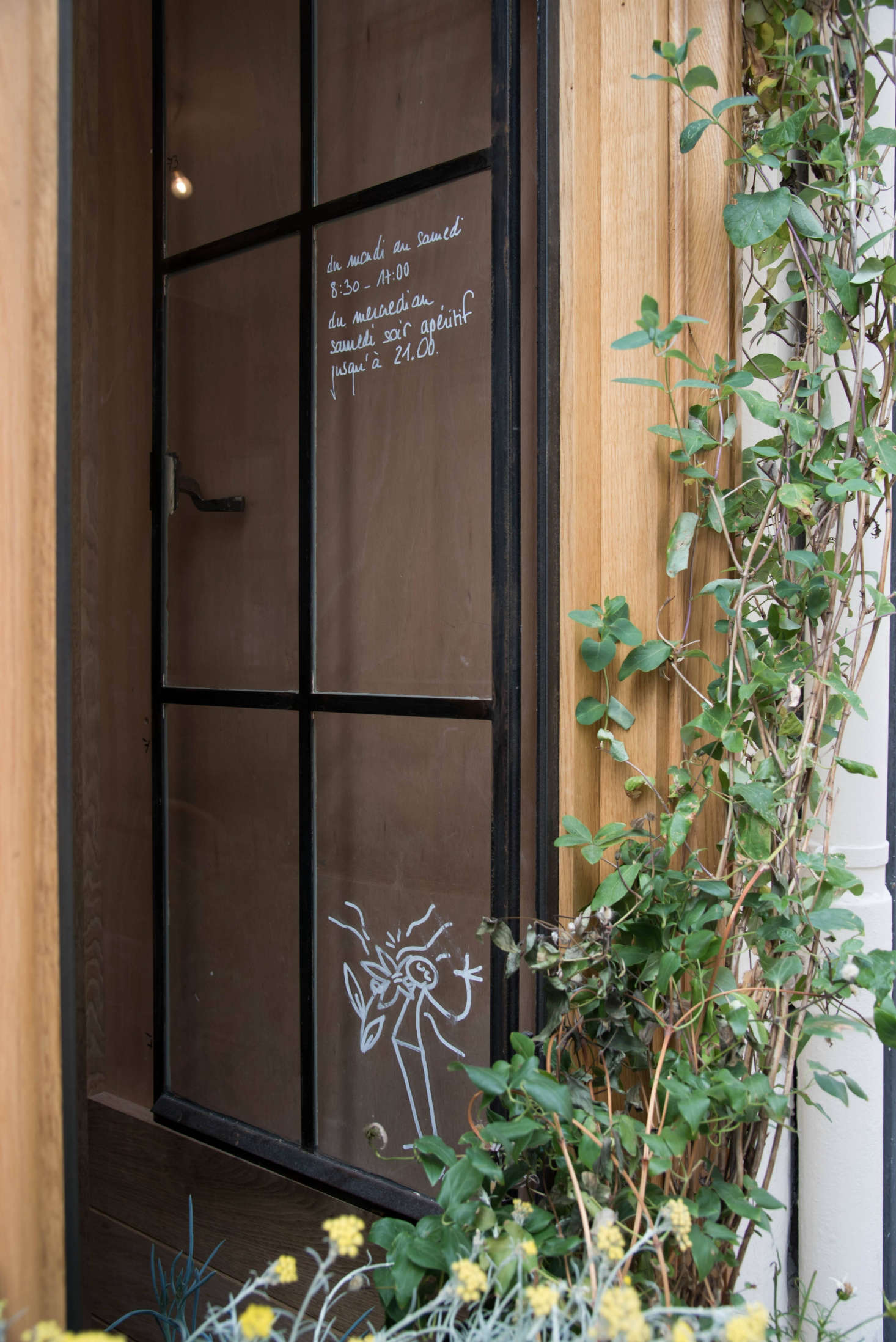 Steel-frame windows double as handwritten signs—and a place for quirky, almost hidden doodles by Paris-based artist YAK.