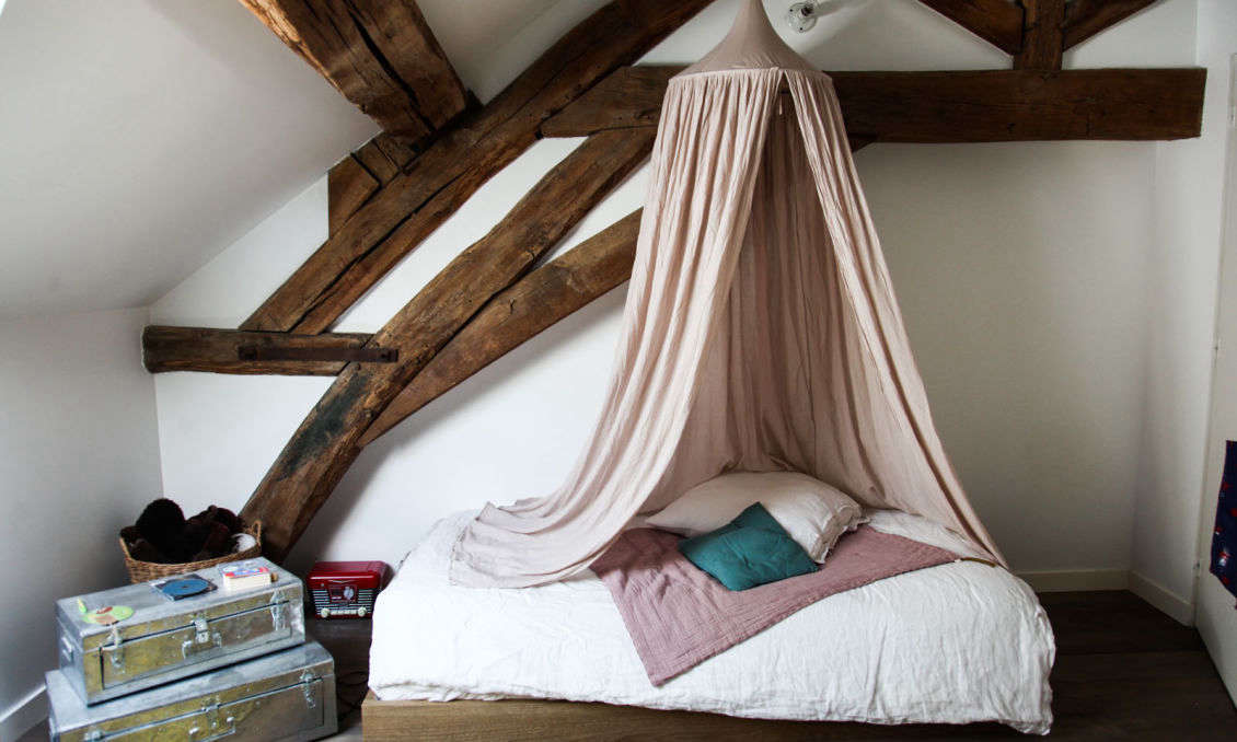 A hanging cotton Bed Canopy is paired with linen bedding, all from Numéro 74 and available from Smallable (see The Smallable Apartment in Paris for more). The steeltrunks are Chinese.
