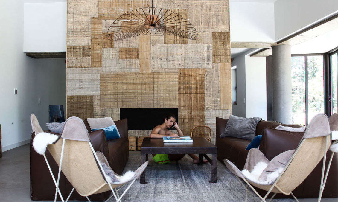 The ground floor is an open-flow, door-free series of living and dining rooms. Prudent created a patchwork hearth using woven bamboo wallpapers, a stylish reference to the house&#8