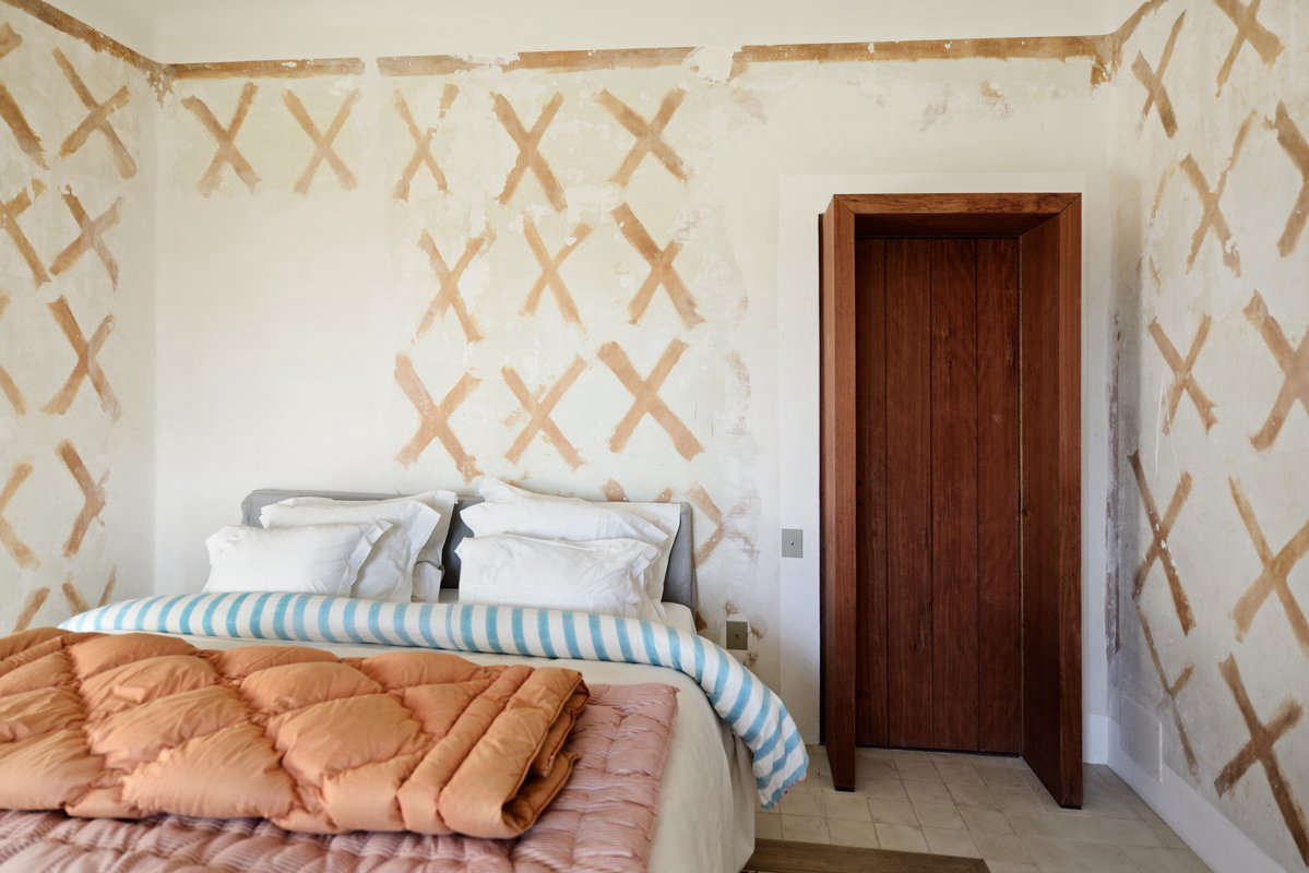 """Adding improvisation to the design process, architects and designers are exposing beams, rough plaster walls, and whatever else is found beneath superficial surfaces. Designer Deborah Ehrlich explains the appeal; she likes the """"archeological history of it."""" Here, old wallpaper glue makes an X-shape pattern in a Provence house by LSL Architects."""
