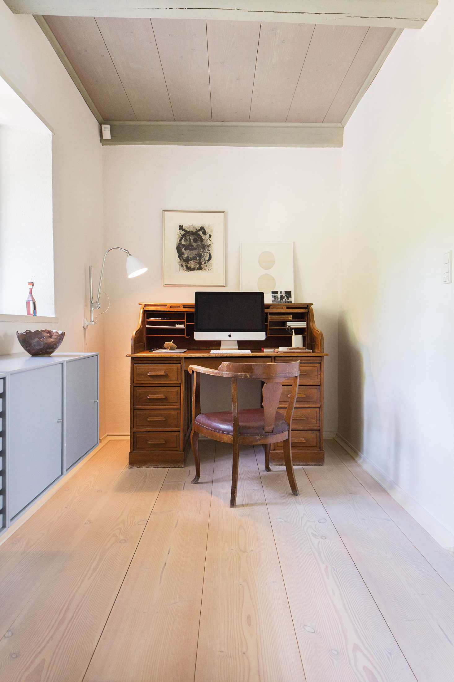 An old-fashioned secretary desk and vintage chair contrast nicely with modern pieces. Photograph courtesy of Dinesen, from The Dinesen Family House: A Historic Renovation for Danish Design Royalty.