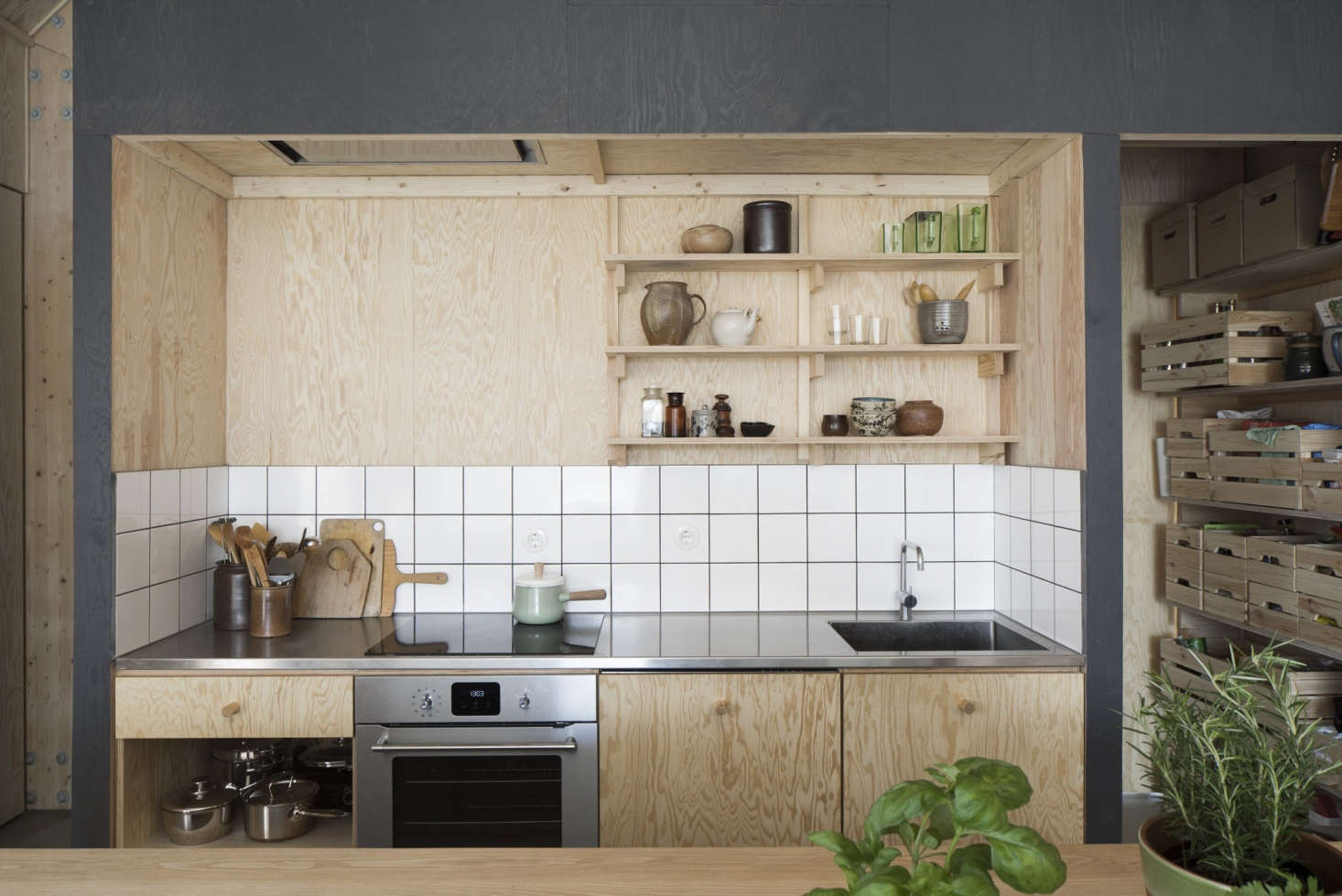 An inset plywood backsplash, shelves, and cabinetry in A Cost-Conscious House in Sweden That's a Pinterest Sensation.