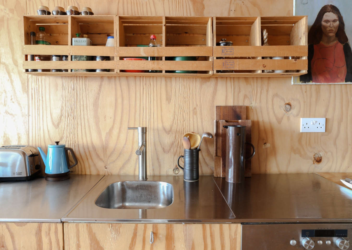 The couple rebuilt the kitchen using Ikea cabinets that they faced with plywood. The stainless steel counter and sink are also from Ikea.