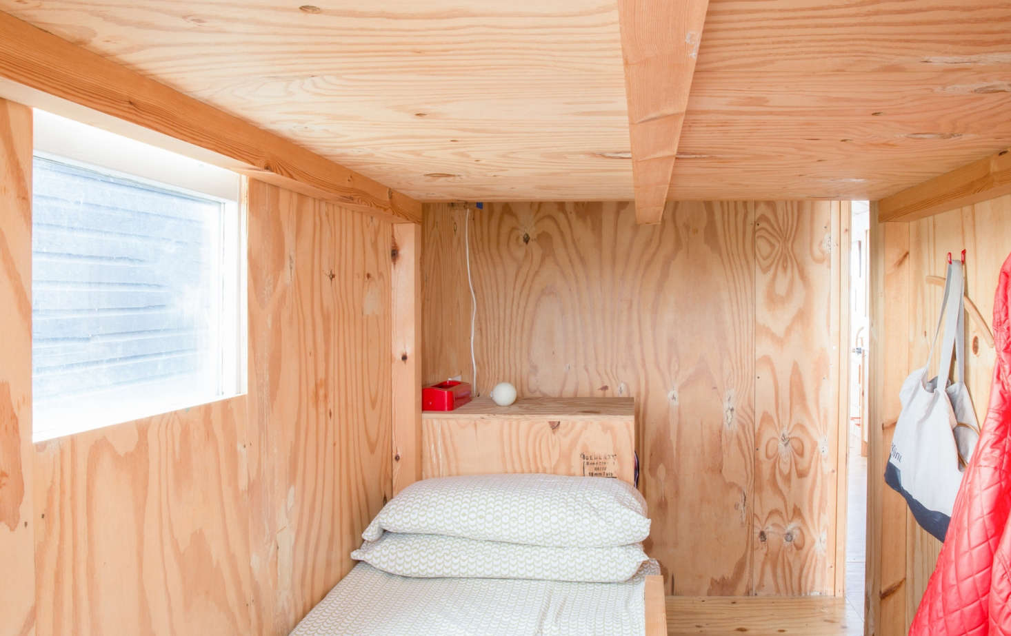 The bedroom has a twin bed and a sleeping loft big enough for two. In addition to wall hooks, there are storage bins incorporated into the steps to the loft.