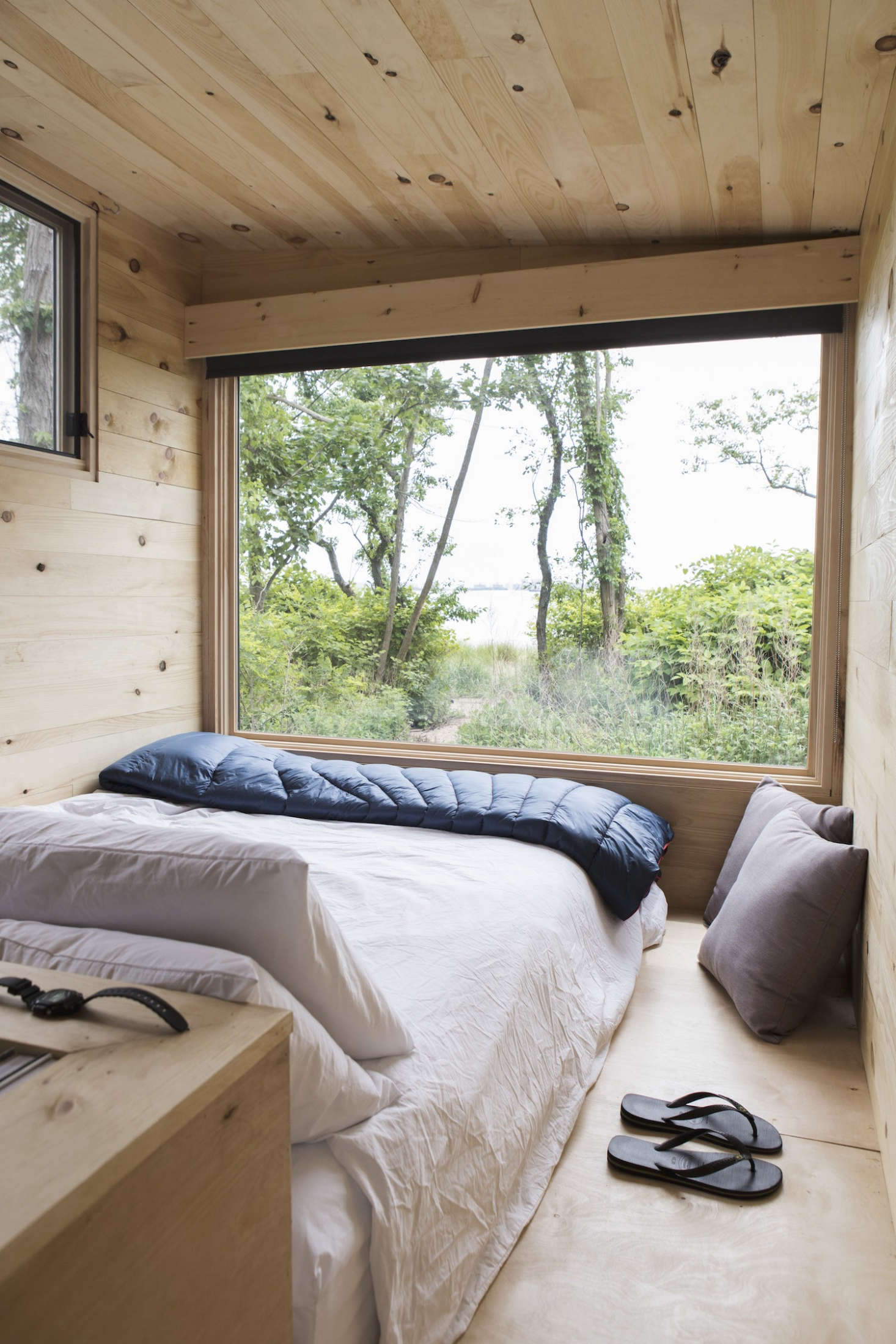 A queen bed in a NYC shoreline pop-up cabin. Photograph by Pine & Palm Journal.