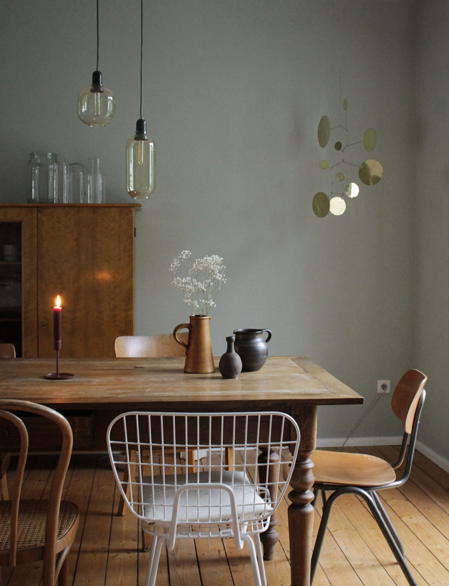 Mismatched chairs, from bentwood to Eames to a school relic, surround the table. The large armoire enables the couple to keep their kitchen pared down. Recognize the Brass Dots Mobile? It&#8