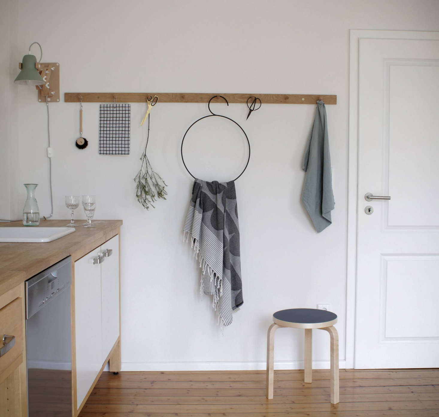A Shaker peg rail from Artilleriet in Gotenburg, Sweden holds a Redecker Dish Brush, House of Rym hand towel, and other sink accessories. The round wire hanger is the Tangent Hanger from Stilleben.