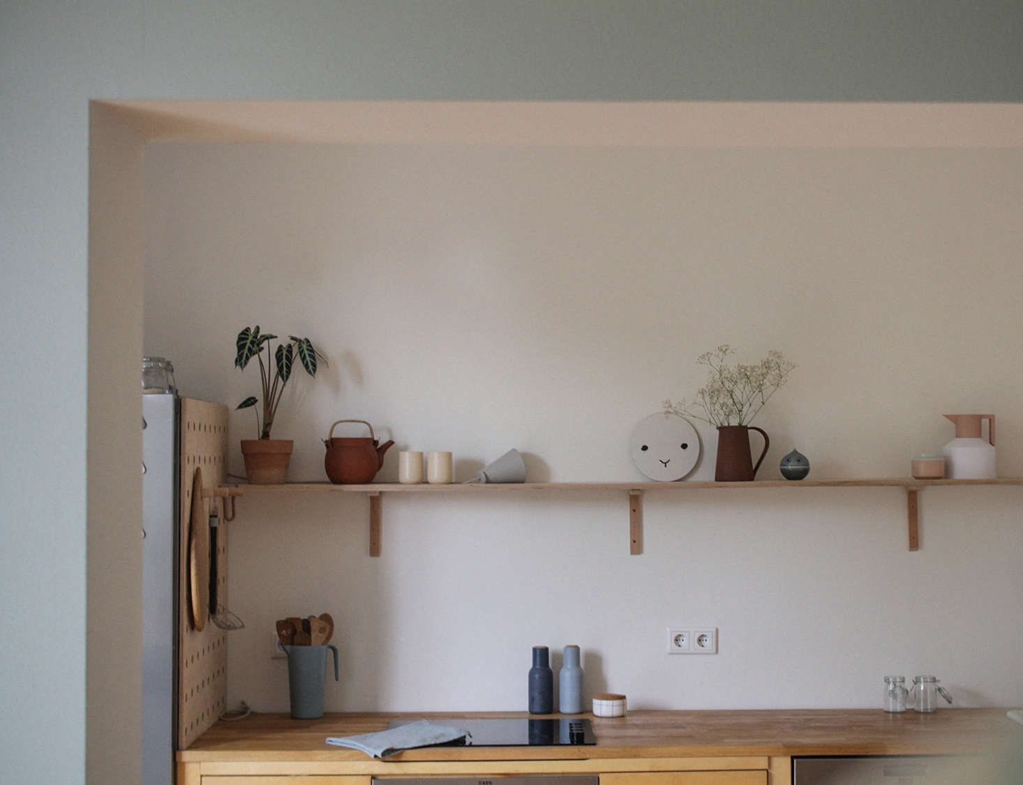 The shelf is stocked with pieces by fellow creatives, including a pair of LAND Mug by Danish ceramic artist Duedahlm, a Terracotta Pitcher from Another Country, and a Normann Copenhagen Geo Vacuum Jug.