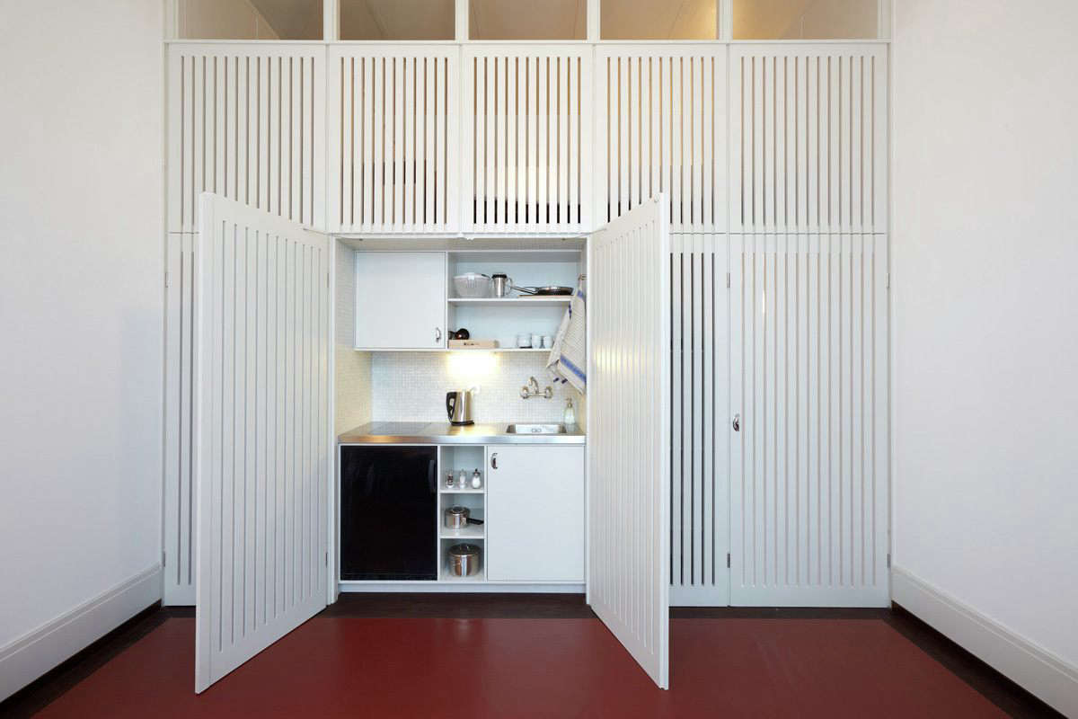 A small kitchen concealed behind slatted doors in a musician's apartment in Basel, Switzerland, designed byBuol & Zünd. Photograph byMichael FritschiofFoto-werk.