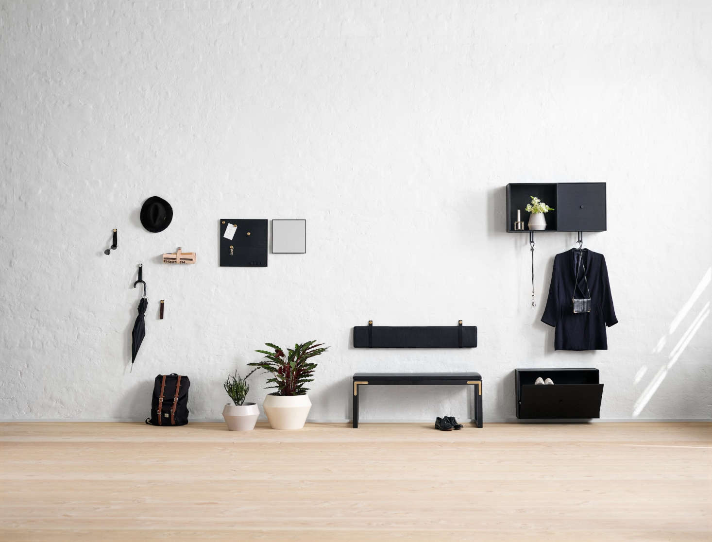 The collection features pared-down solutions for the entryway or hall. Shown here: An elongated landing pad featuring the Conekt Bench (with wall-mounted backrest available in leather or textile) and wall-mounted Frame Shoe Cabinet.