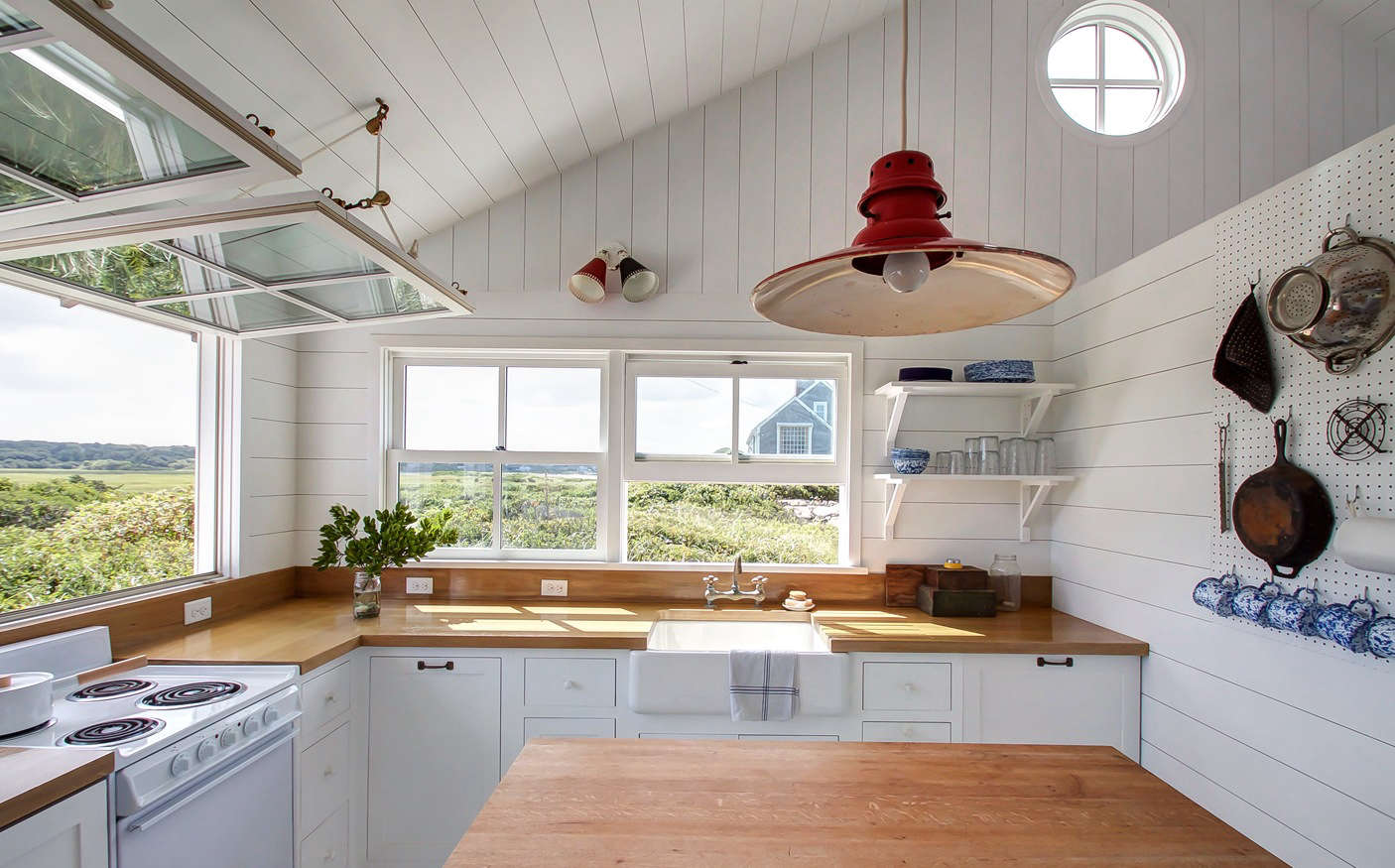 The light fixtures are all vintage; a double sconce from Amsterdam and a red barn light from 1st Dibs (for something similar, look to Barn Light Electric). The countertops are oak finished with a marine varnish. On the white electric range sits a Kaiko One-Handle Pan by Japanese designer Makoto Koizumi.