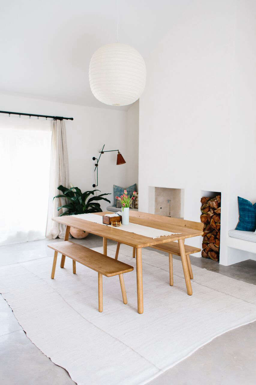 The dining table and benches are by English brandAnother Country. The interior paint is a custom mix, but the closest standard match is Glacier White from Benjamin Moore.