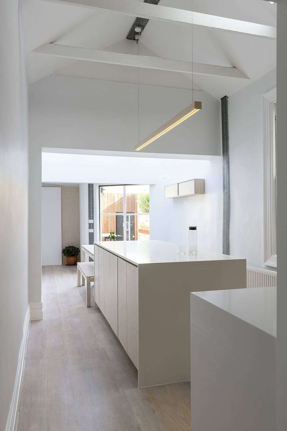 In the narrow, open-plan kitchen and dining, there's no room for transitions in decor. Henkell kept the look as consistent as possible by designing custom furnishings: a dining table and benches, a wall-mounted storage cabinet, plus a pendant light overhead, all linear in form and made of matching plywood.