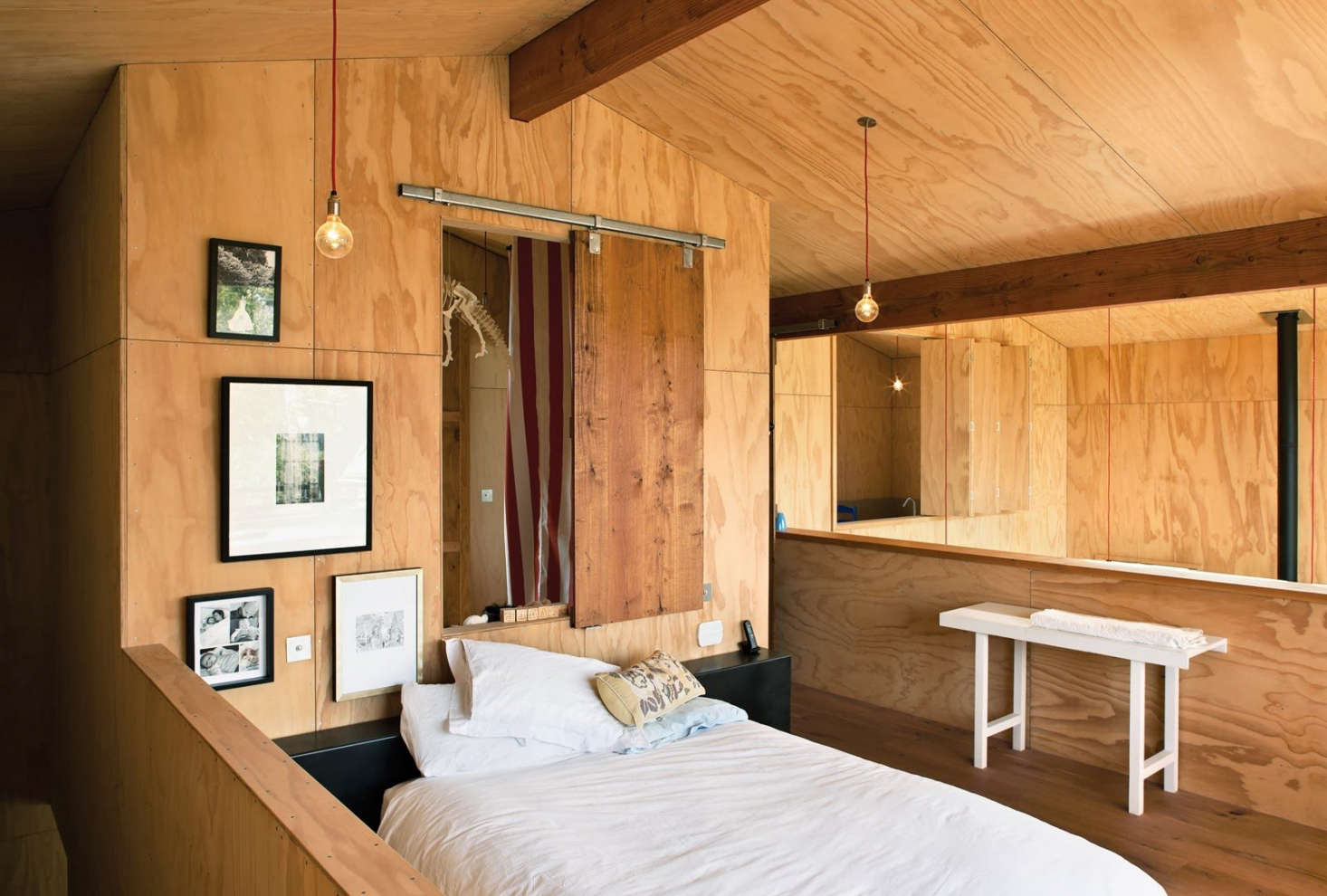 A sliding barn door made from oak floor boards becomes a feature in a bedroom clad in plywood, by architect Davor Popadich on Auckland's North Shore. Photograph by Simon Devitt.