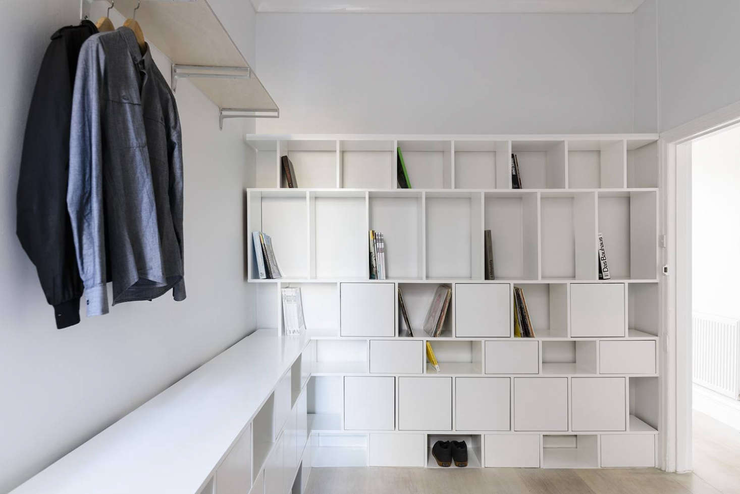 "Not every bedroom needs a closet and chest of drawers. Henkell installed a wall of white MDF cubbies to give the eventual owner flexible storage space for ""office type"" things like books and magazines in addition to clothes and shoes. ""The room is very small so a conventional deep robe would have been too clunky; instead we opted for this 'thin' storage approach."""