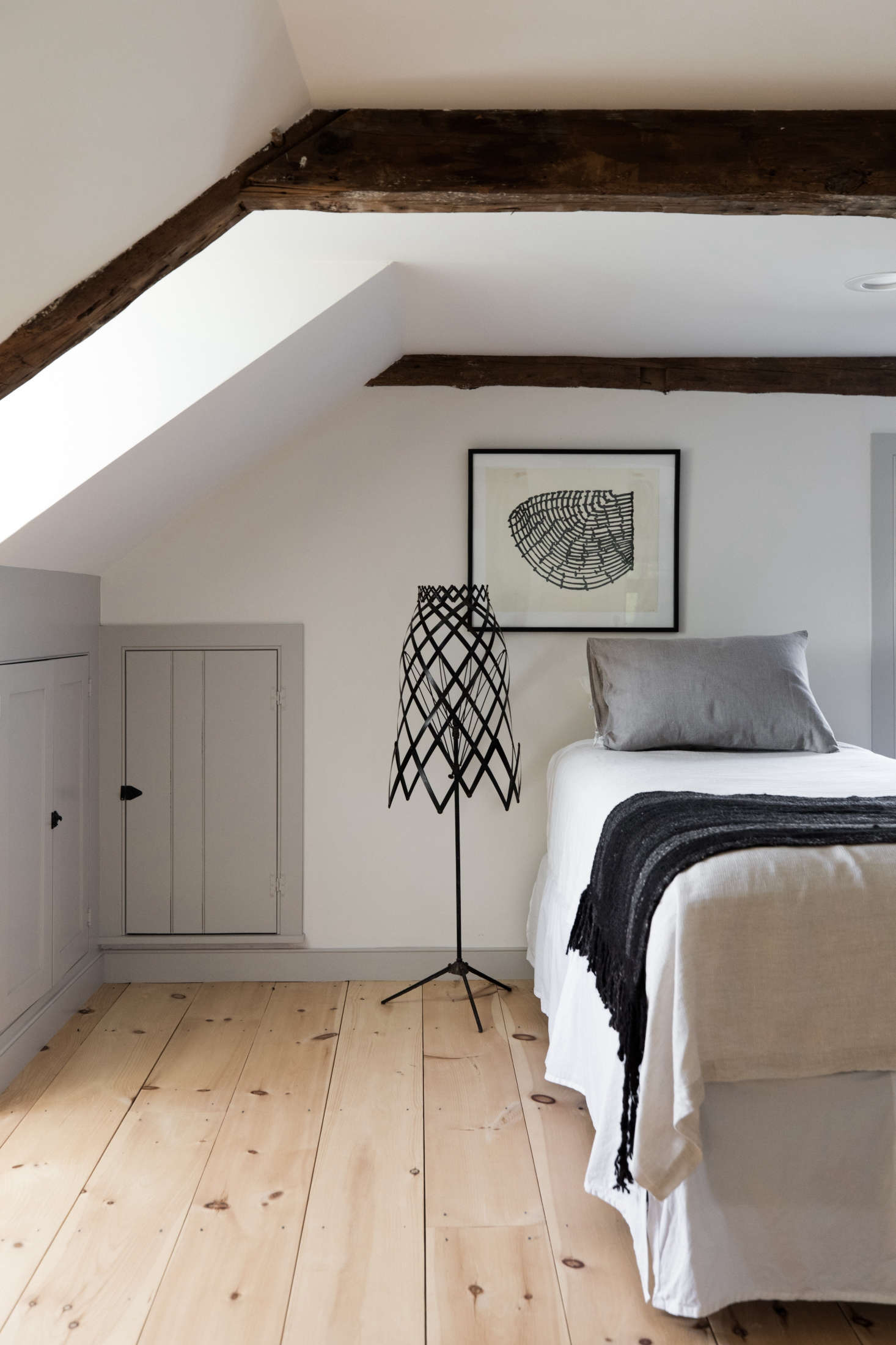 In a narrow bedroom, Esteves preserved the under-eaves cabinets, which his mother uses to store spare blankets.