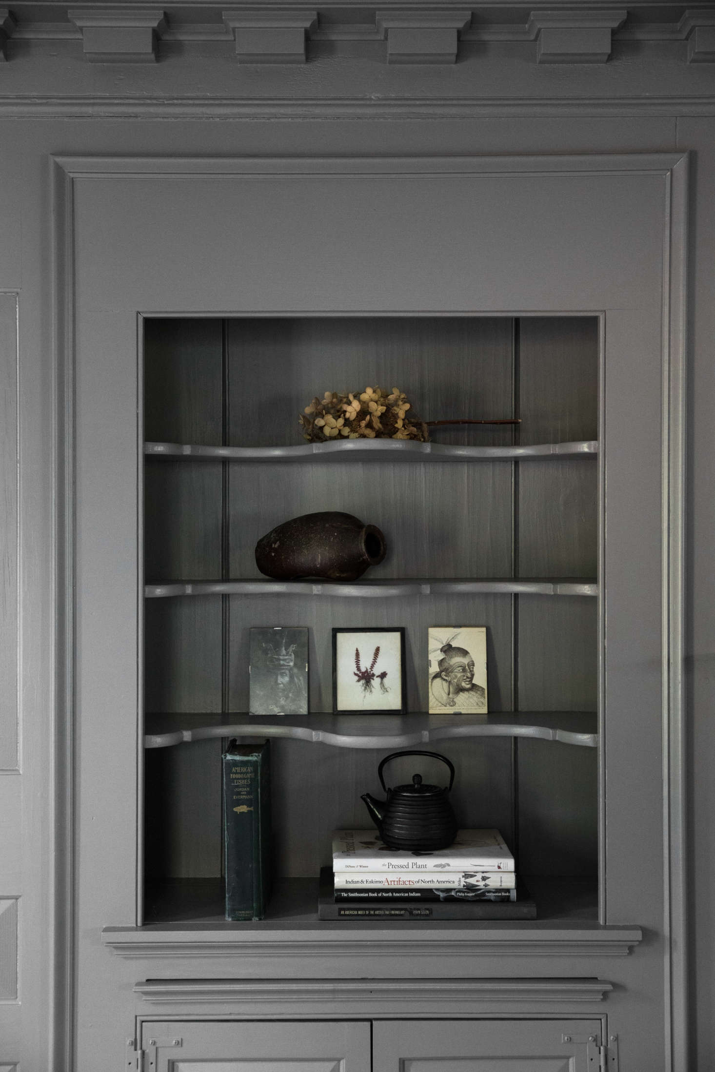 A built-in hutch, painted gray, holds objets d&#8
