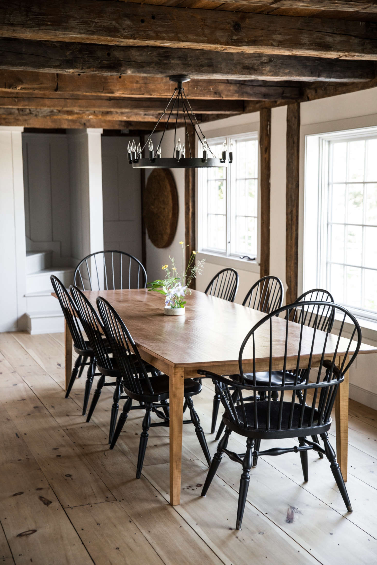 The adjacent dining room, with a farm table and black spindle-backed chairs. The centerpiece is made of foraged blooms arranged by Esteves&#8