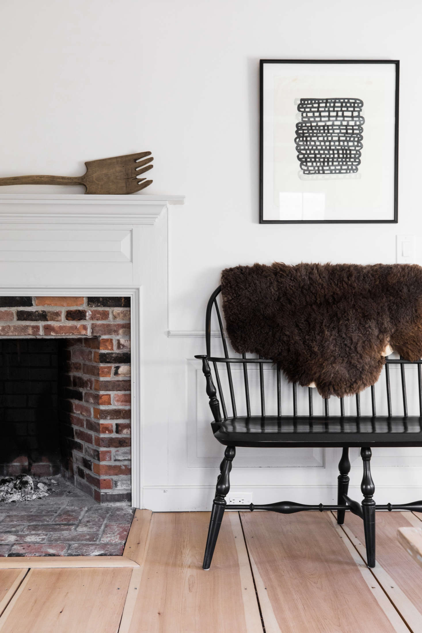 Beside another fireplace, a black bench fromWindsor Chairmakers in Lincoln, Maine. The print is by Maine artist Anna Hepler.
