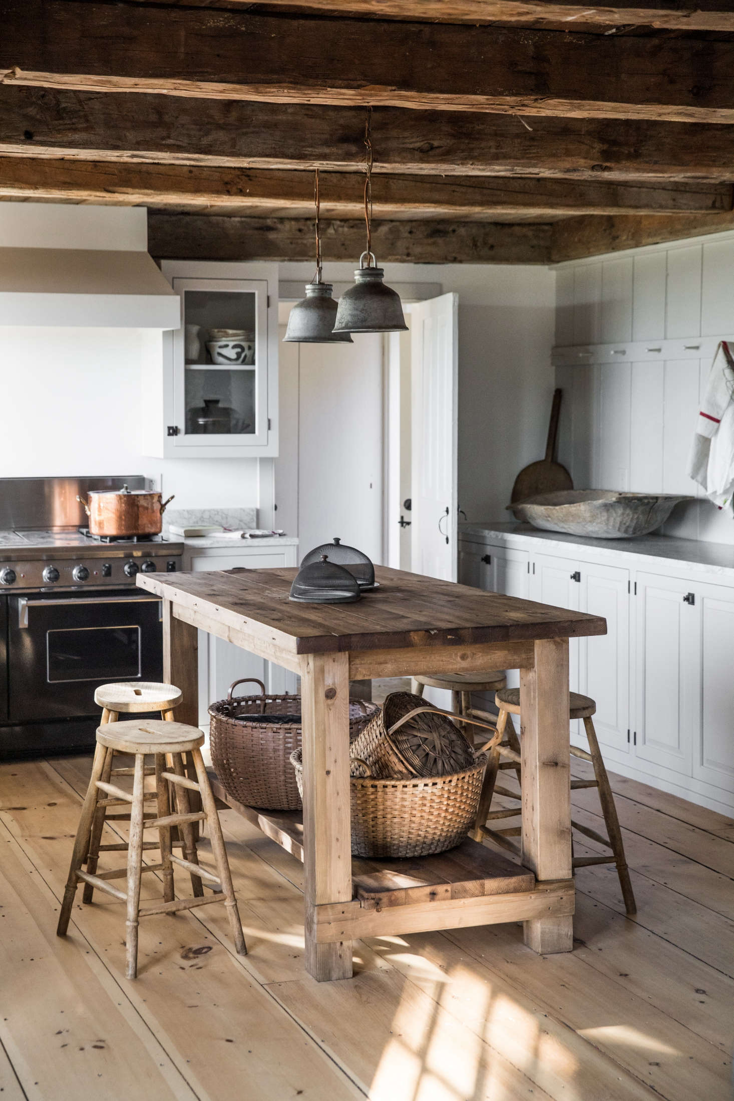 Esteves lined a wall of the kitchen with a Shaker peg rail. Clean towels are stored in the round baskets under the island. The wire cages were sourced from Trillium Soaps and the wooden stools were another Marston House find.
