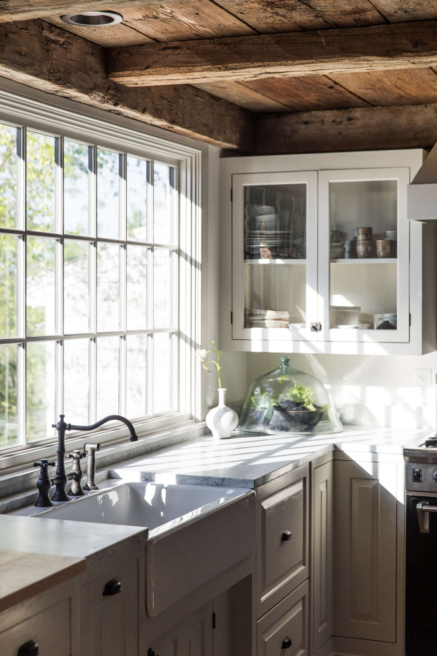 In the kitchen, light filters in through the original paned windows.