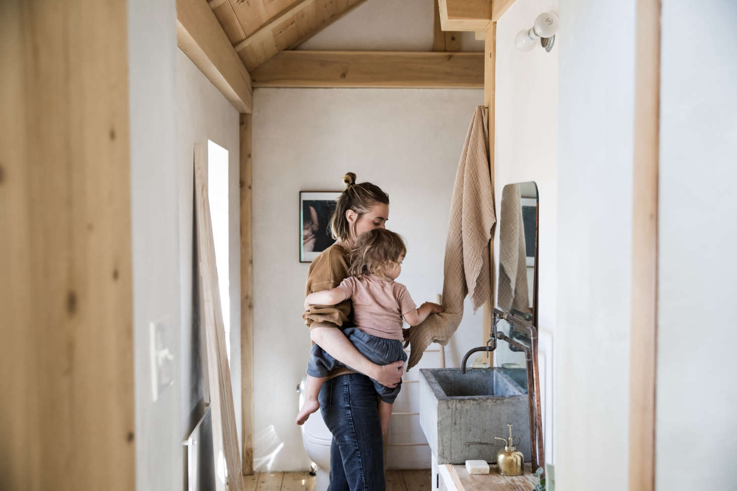 O'Rourke and son Diogo in the bathroom, with an exposed-pipe faucet and concrete sink.