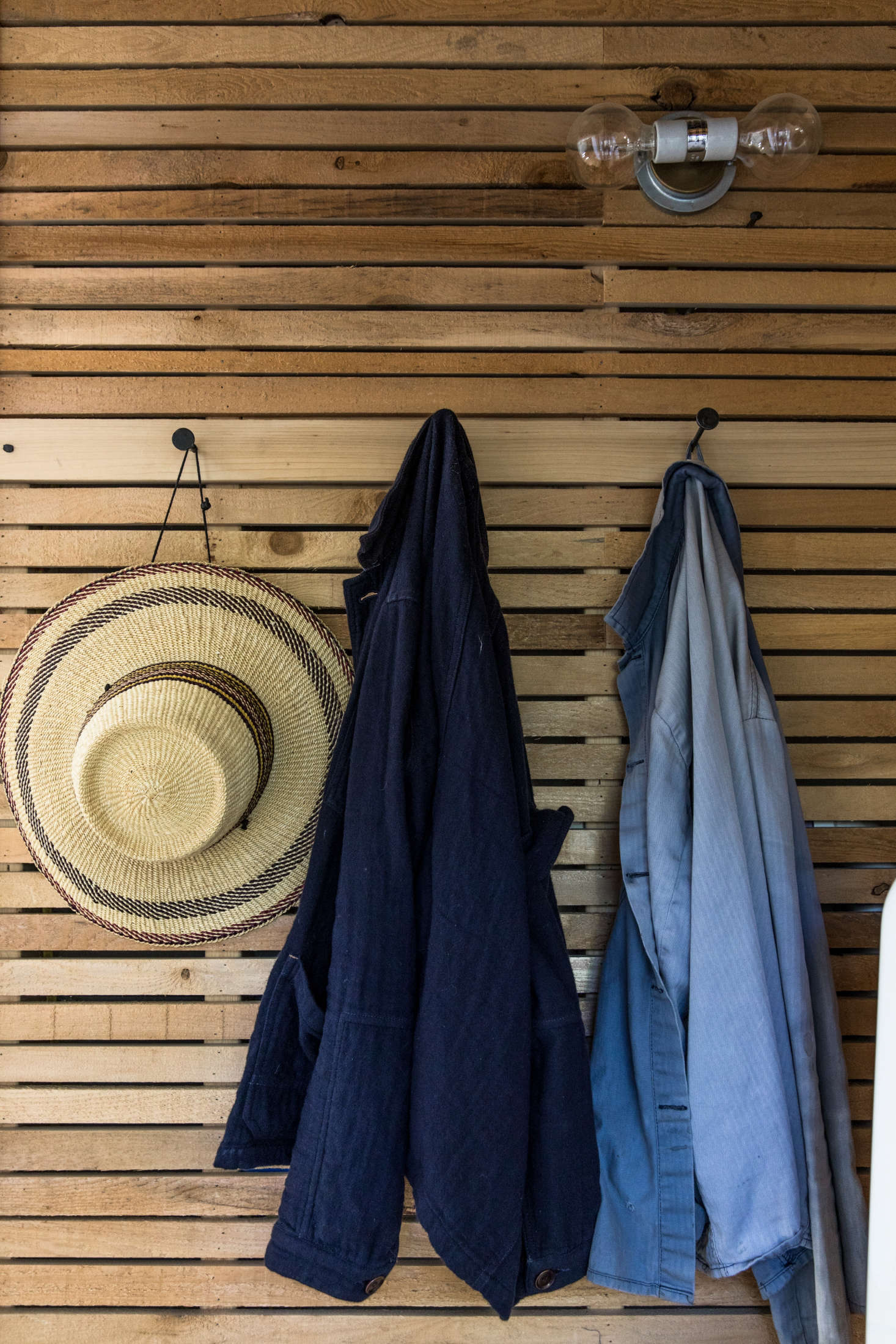 Work shirts hang on hooks from Sugar Tools in Camden, Maine. The pared-down lighting fixtures throughout the house are theU/data-src=