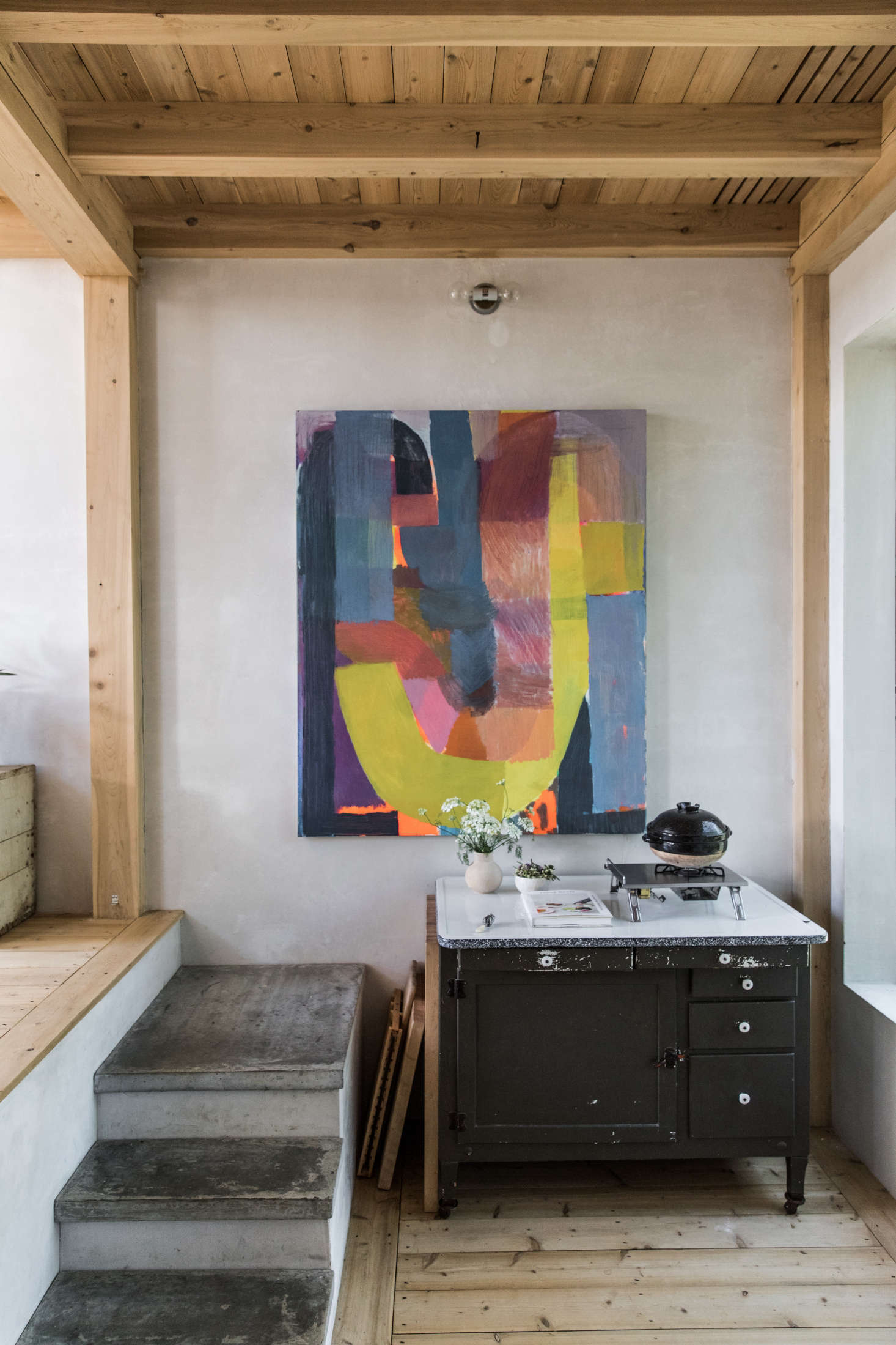 At the other end of the kitchen, a small cooktop sits atop a vintage cabinet.