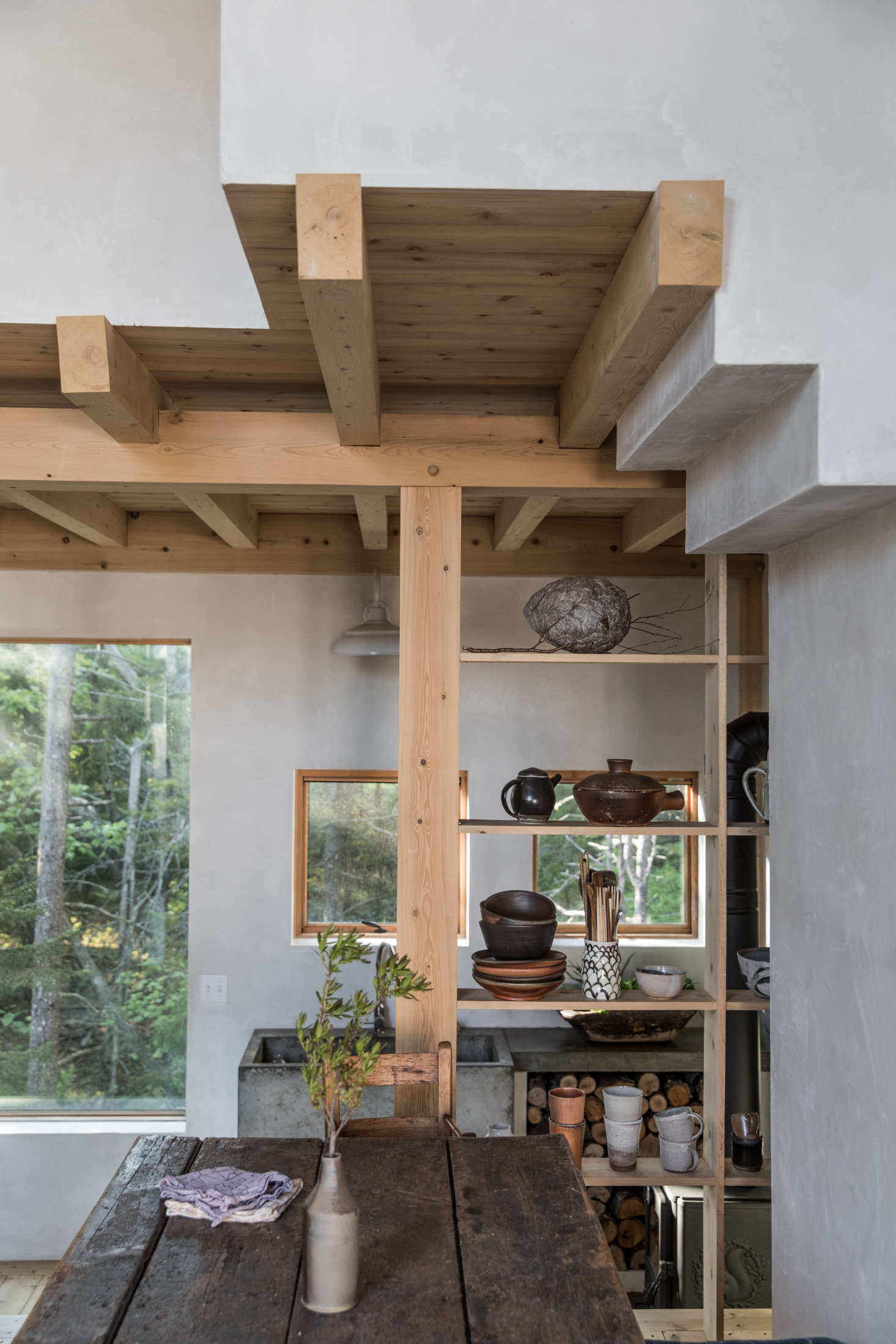 Open cedar shelves create a divider between the dining room and kitchen and display earth-toned ceramics.