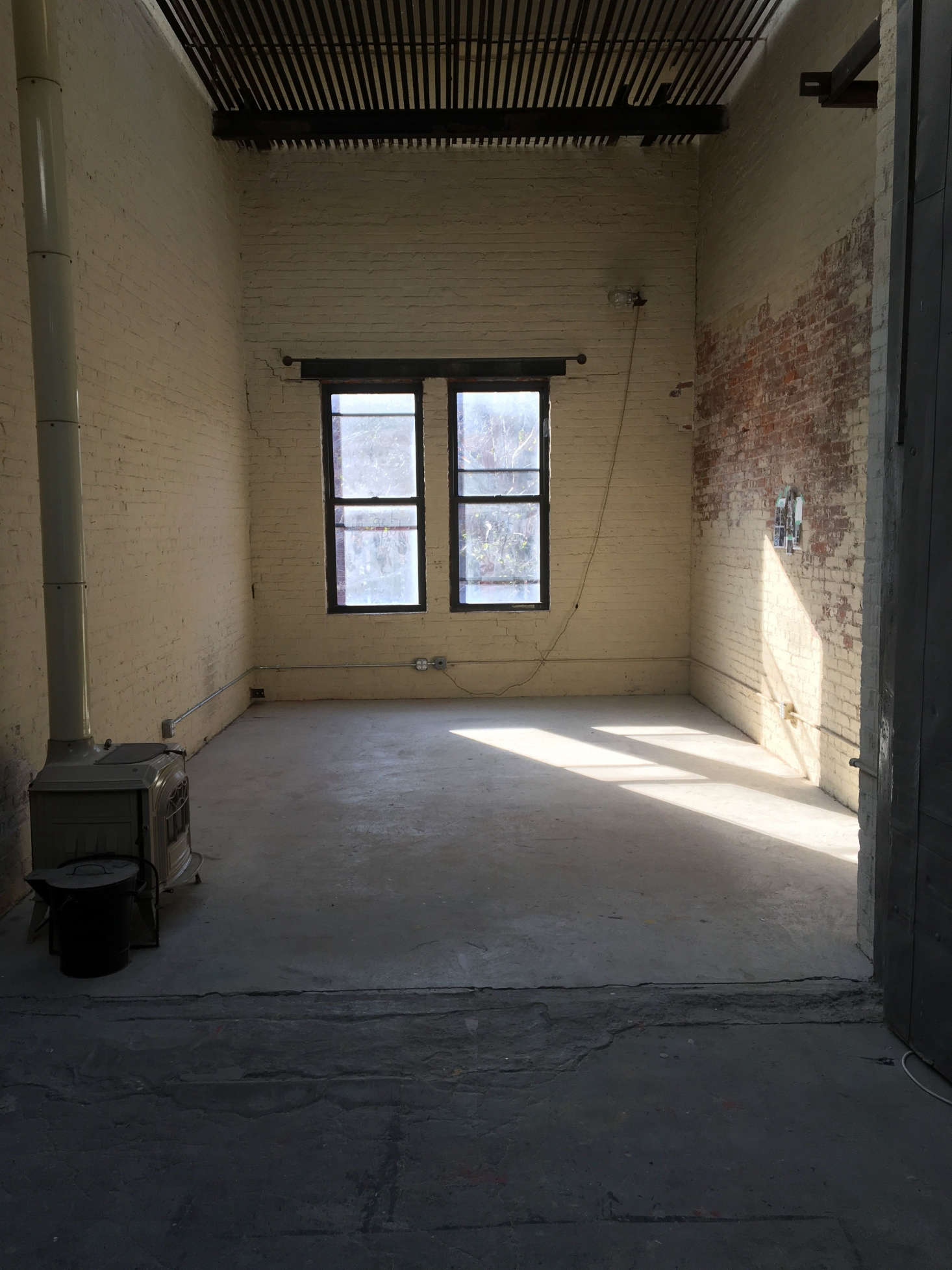 """When my landlord took over the building , it had no interior walls—it was one big open factory floor,"" Mannix says. ""When I discovered the space in 2016, it was very raw; the paint was chipped and the roof leaked when it rained. Back then it was being used by a costume design team as a temporary office."" The Cook Space team preserved the charming woodstove, painted the brick, and transformed the bare-bones space into a space celebrating cooking—and design. Photograph courtesy of Cook Space."