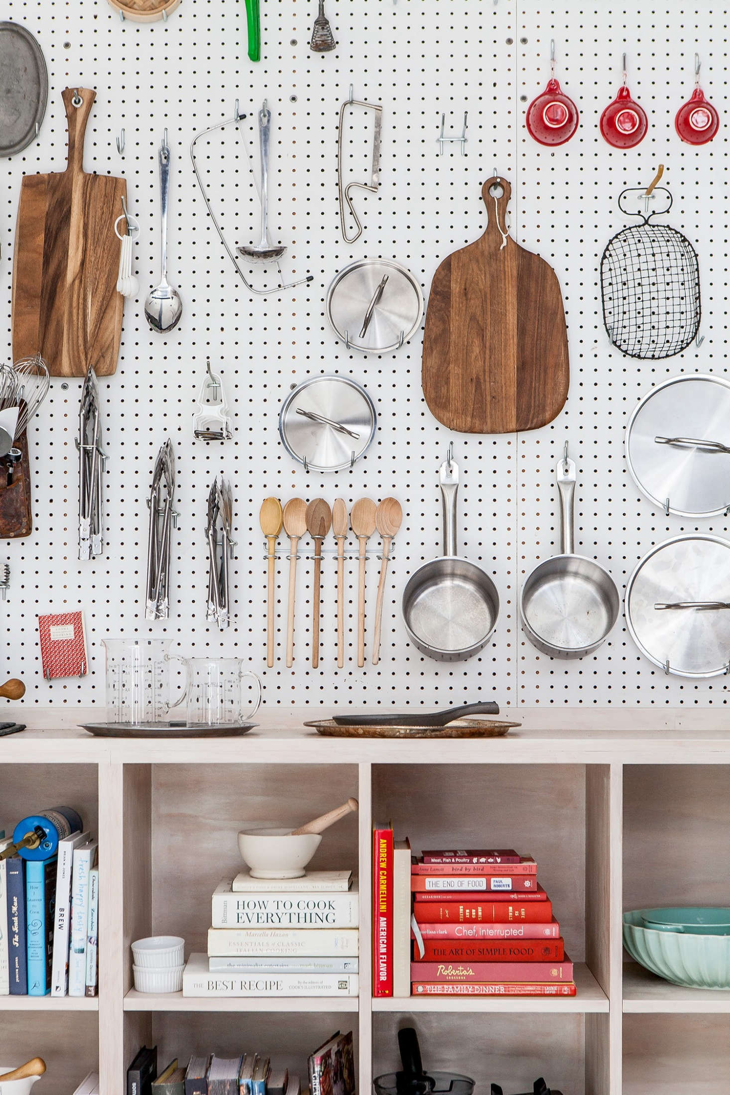 The satisfyingly compartmentalized pegboard at Cook Space in Brooklyn is home to wooden spoons that do double-duty as kitchen tools and decor. Photograph by Sean Santiago from The Effortlessly Cool Chef's Apartment: 9 Ideas to Steal from Cook Space in Brooklyn.
