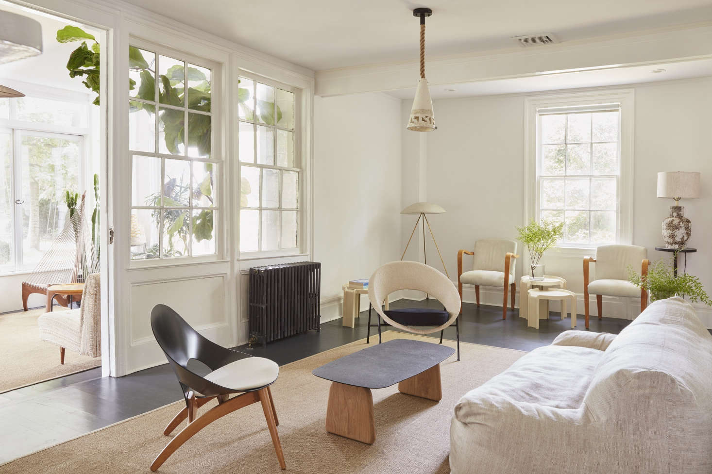The Wood Floors Are Painted Dark Navy And Covered With Neutral Area Rugs To Withstand