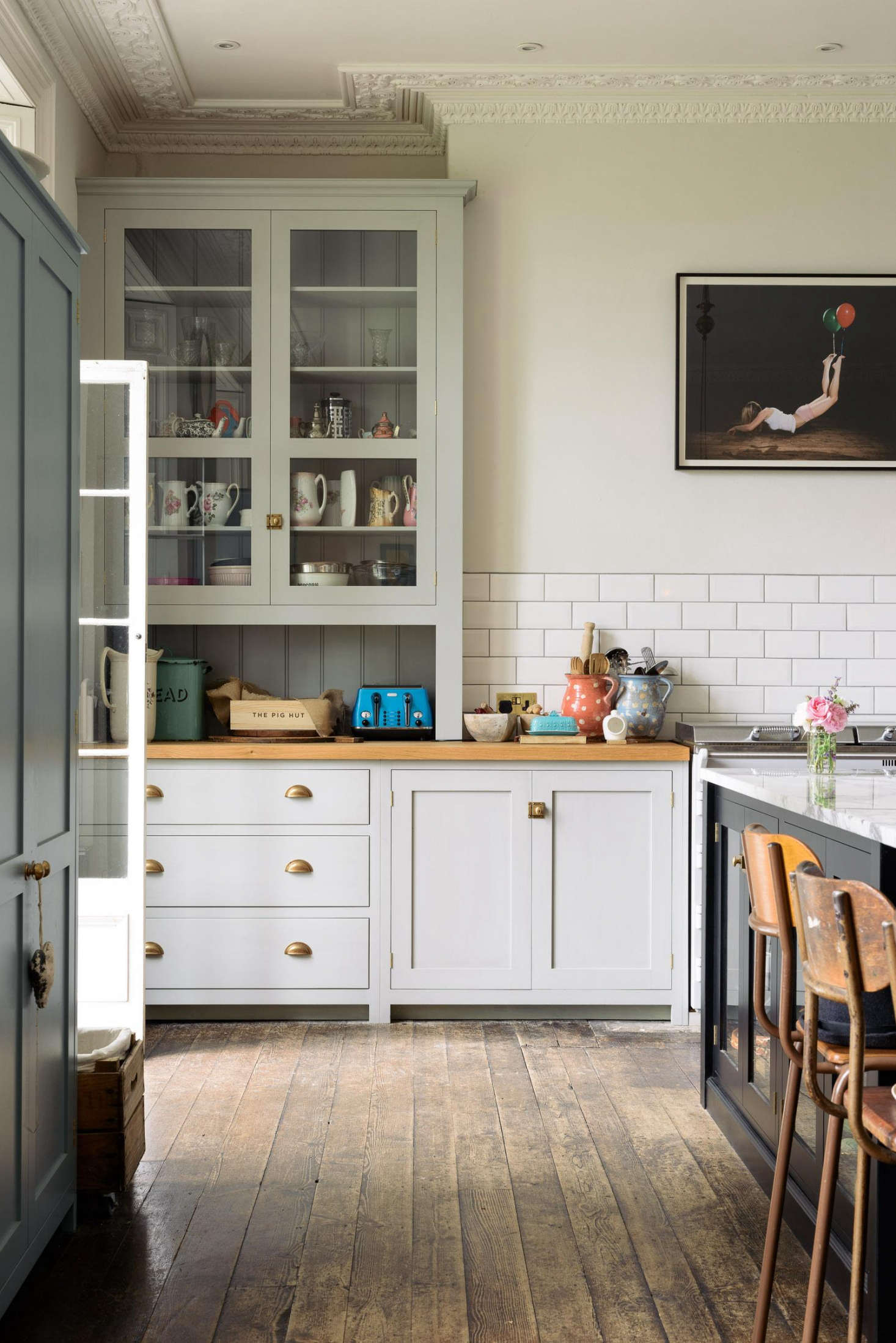 "Lowe chose a combination of deVOL's Classic English and Real Shaker cabinetry, shown side-by-side above. ""The simplicity of the Shaker pieces were perfect to soften the bold and busy marble on the island,"" said Parker. The marble is arabescato vaglia."
