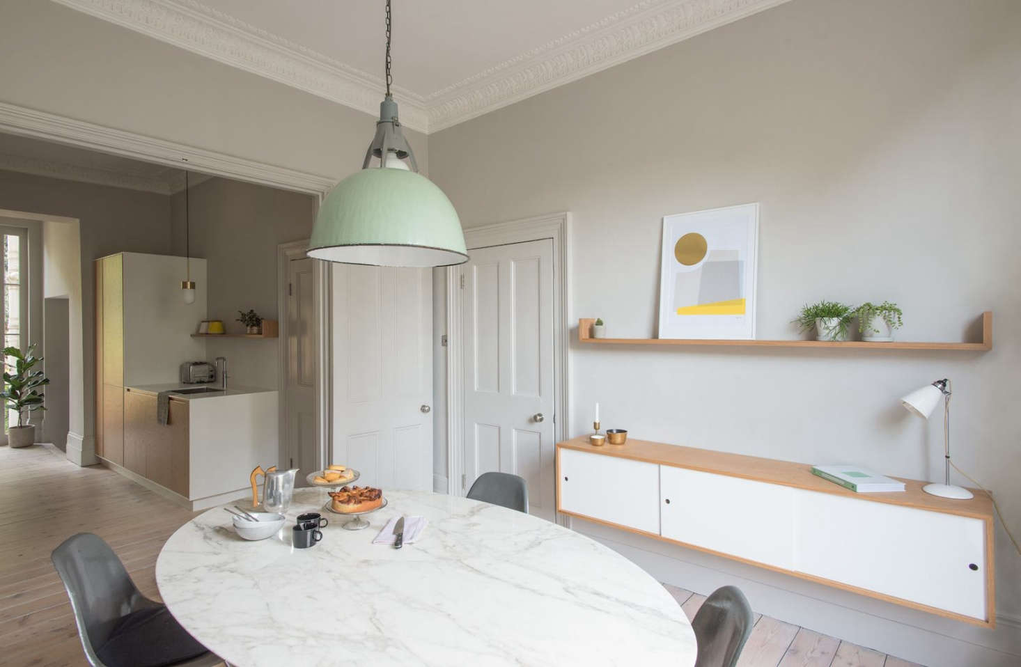 At the other end of the kitchen is a small dining room with a marbleSaarinen Dining Table and a vintage, green enamel pendant light overhead.