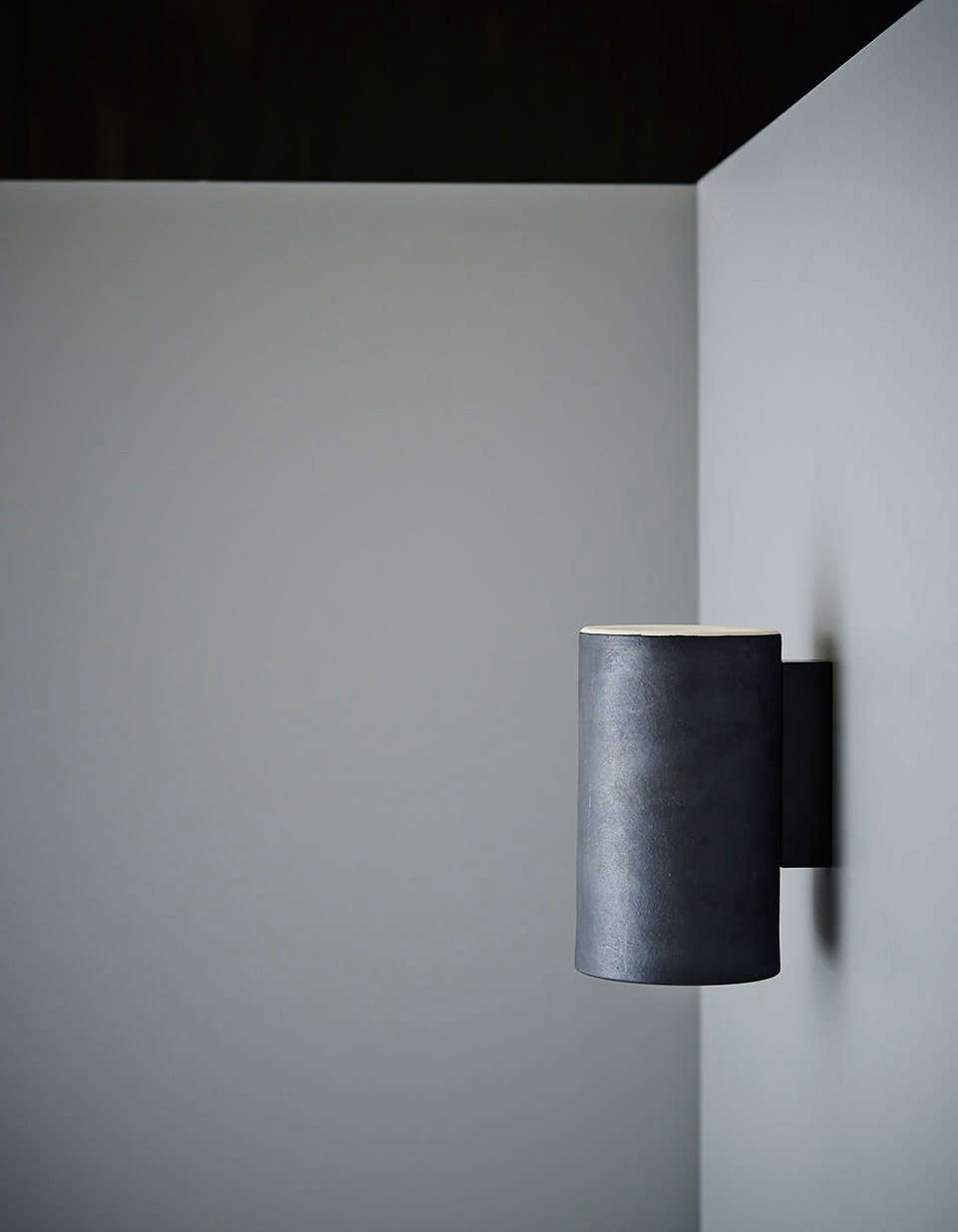 The Earth Wall Light in a charcoal glaze finish.