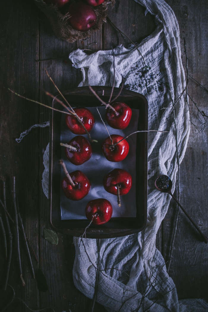 Candied apples are made creepier with dead branches as handles.