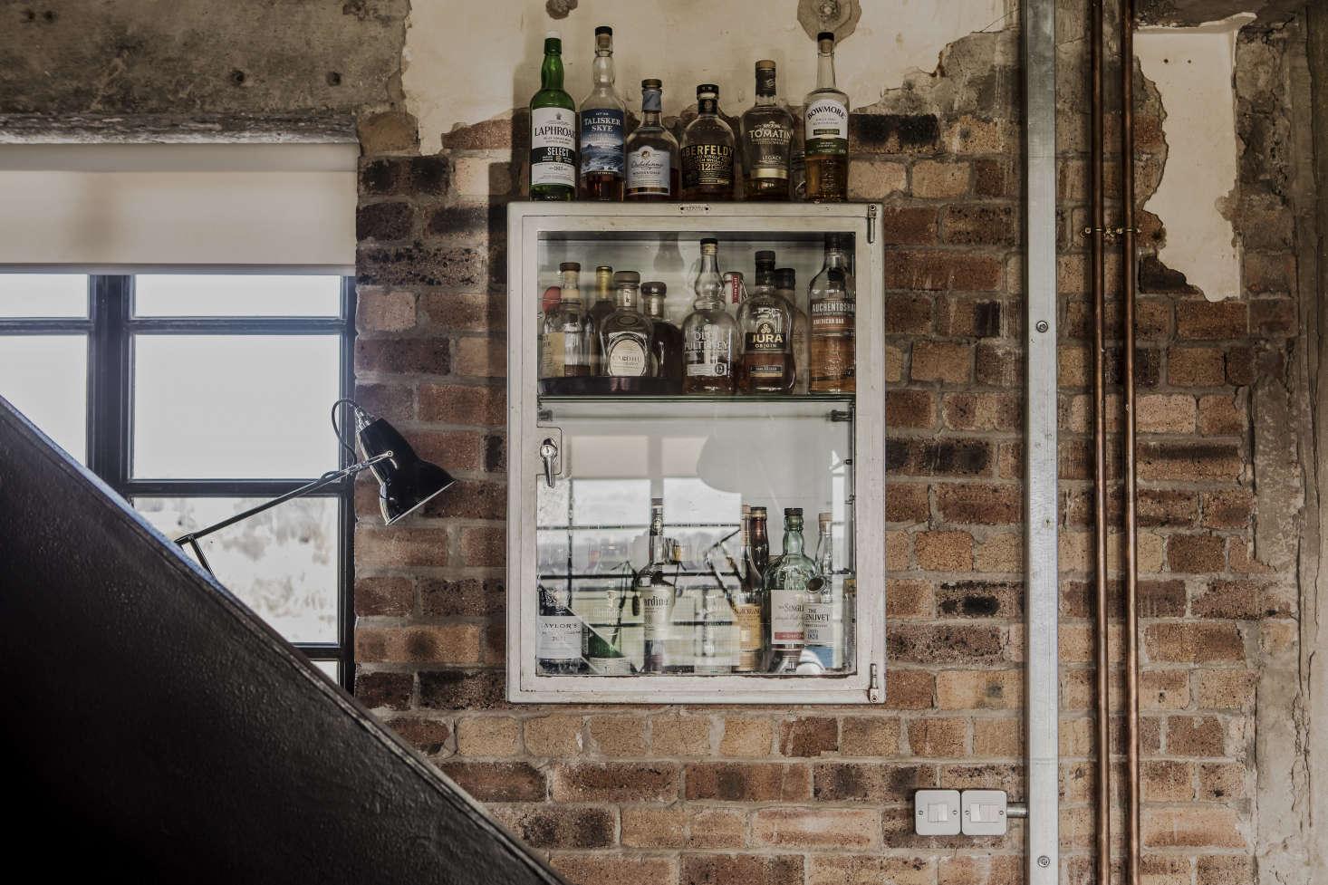 A vintage medicine cabinet serves as a liquor cupboard.