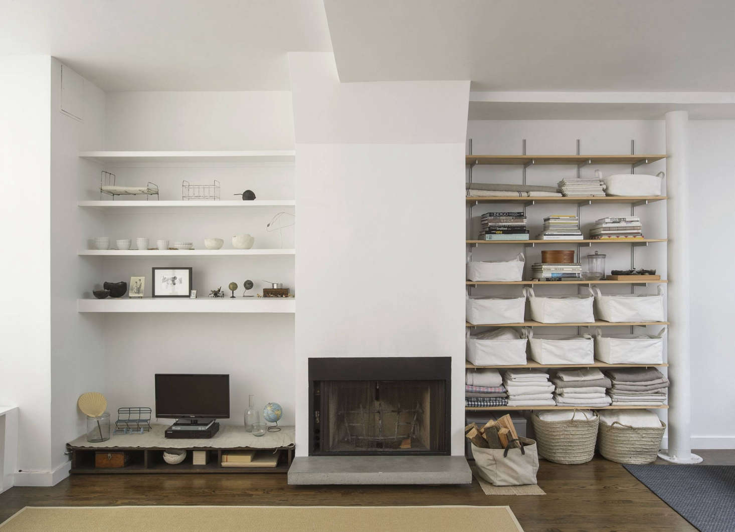 On one side of the fireplace is a small television and collections on display. On the other, built in Rakk shelvingholds stacks of linens, old issues of Selvedge magazine, Japanese pattern books, and art biographies on Rei Kawakubo and Henri-Cartier Bresson, among others.