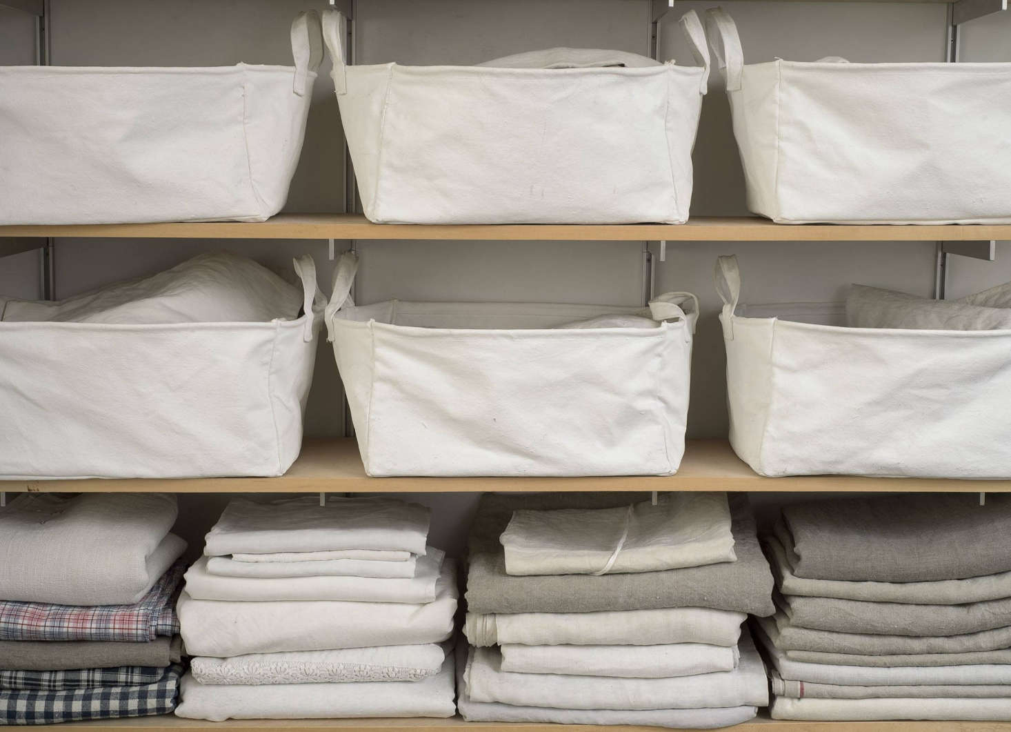 Vintage linens are folded on a shelf below a row of white Serax Canvas Basketsthat holds miscellaneous odds and ends.