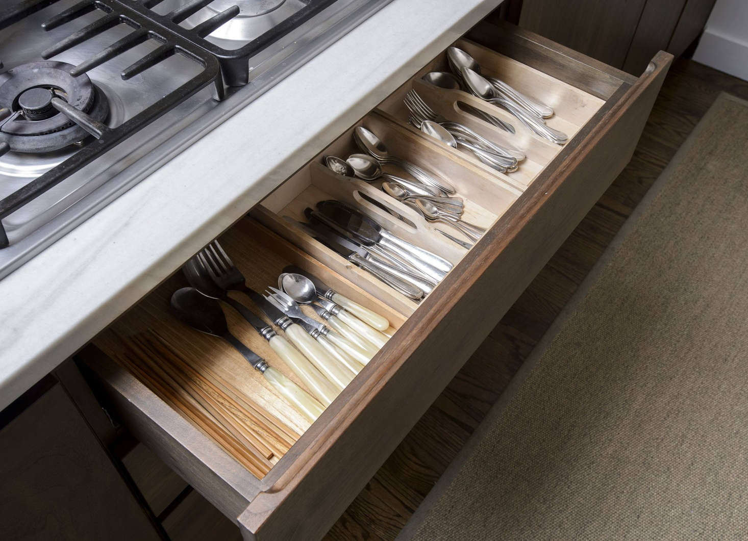 Makié organizes cutlery by type (chopsticks, resin handle flatware, and vintage silver) and size in a drawer beneath the Miele 30-Inch Gas Cooktop. Hidden behind a walnut panel is a Miele Fully Integrated Dishwasher.