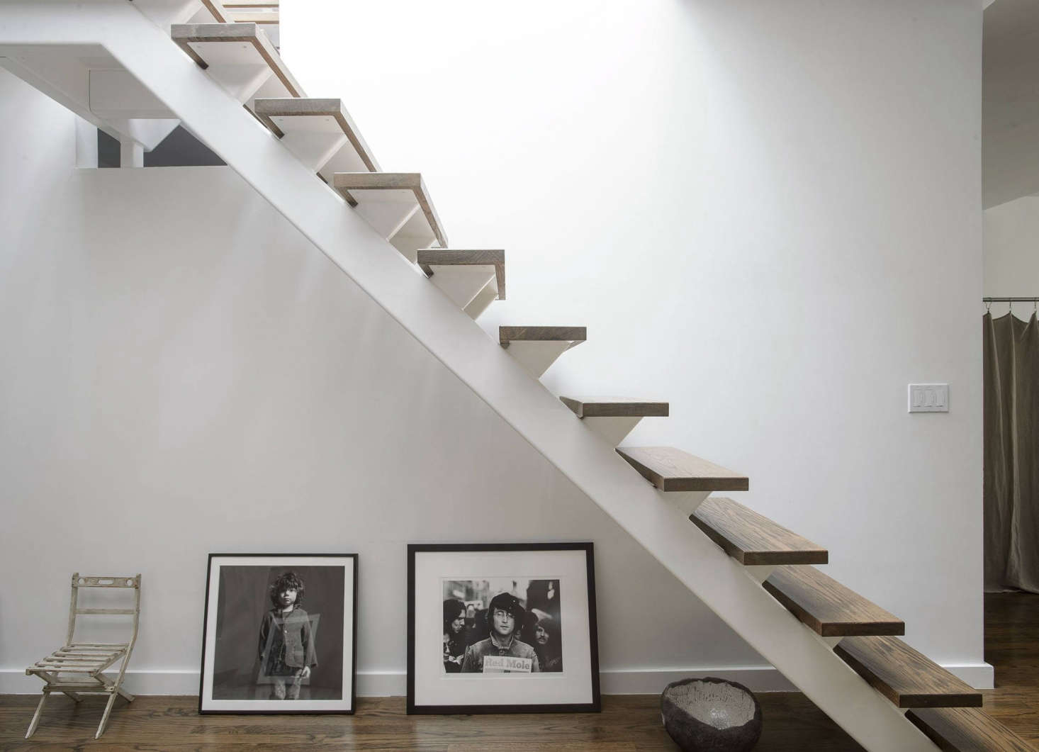 Under the stairs is an antique children's chair; a photograph by Inez & Vinoodh of their son, Charles Star; a Rowland Scherman photo of John Lennon; and a hand-shaped ceramic bowl by artist Genevieve Chevallier.