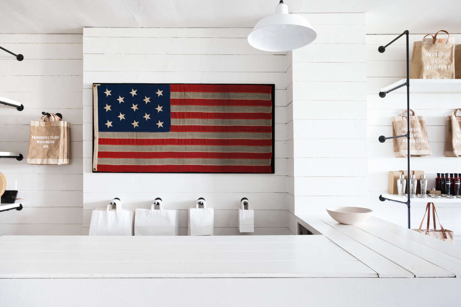A vintage American flag hangs above the retail counter. It's reminiscent of an item in the Salt House online shop: an American Flag Throw; $180.